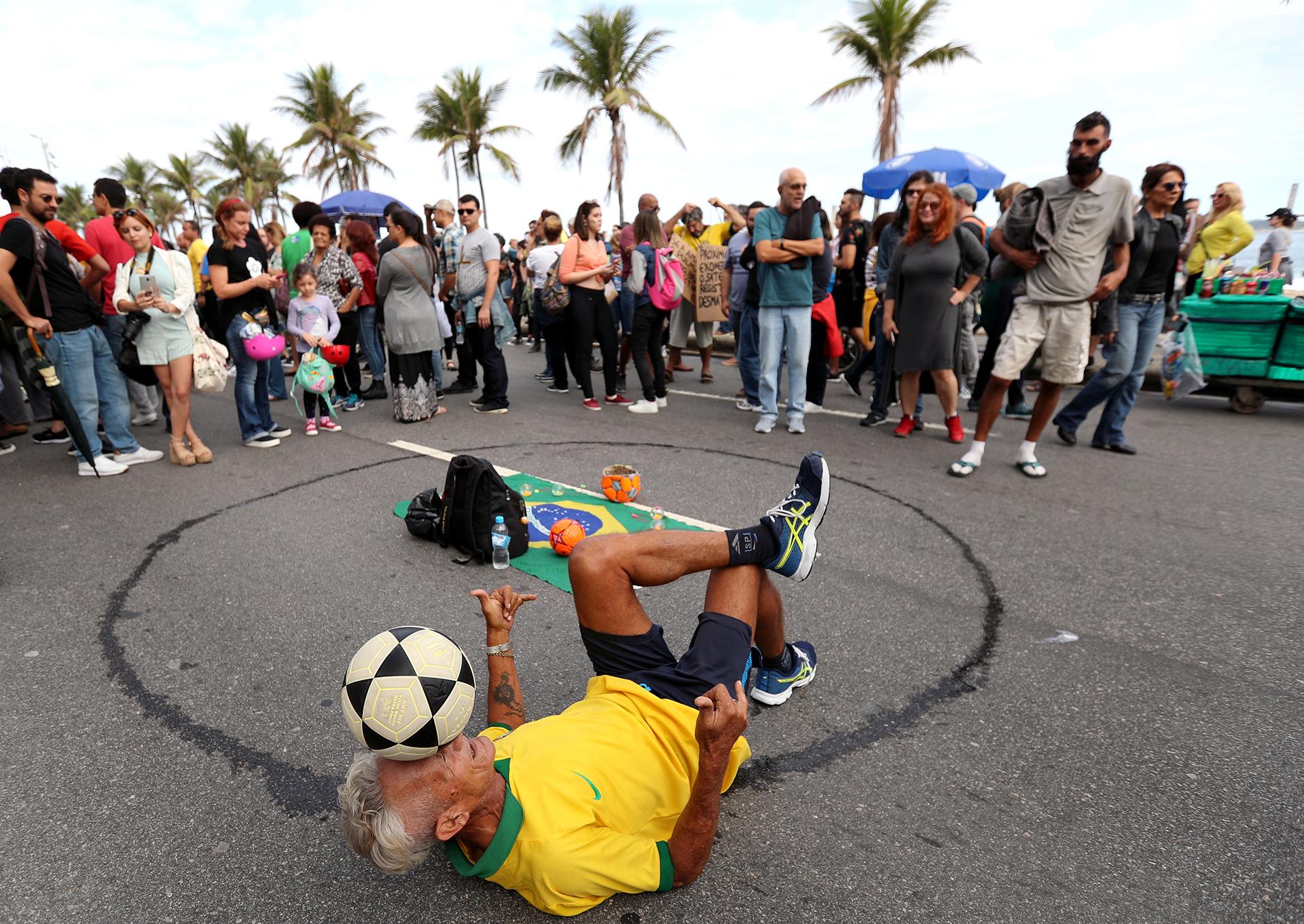 Un hombre juega con una pelota de fútbol durante la manifestación. REUTERS / Sergio Moraes