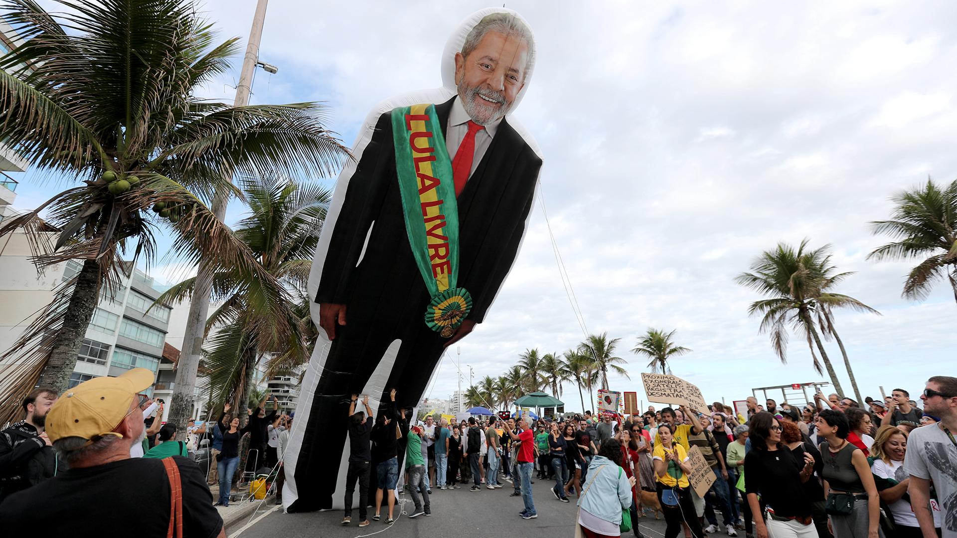 """La gente sostiene una muñeca inflable del ex presidente brasileño Luiz Inácio Lula da Silva antes de la manifestación. La faja dice """"Liberen a Lula"""". REUTERS / Sergio Moraes"""