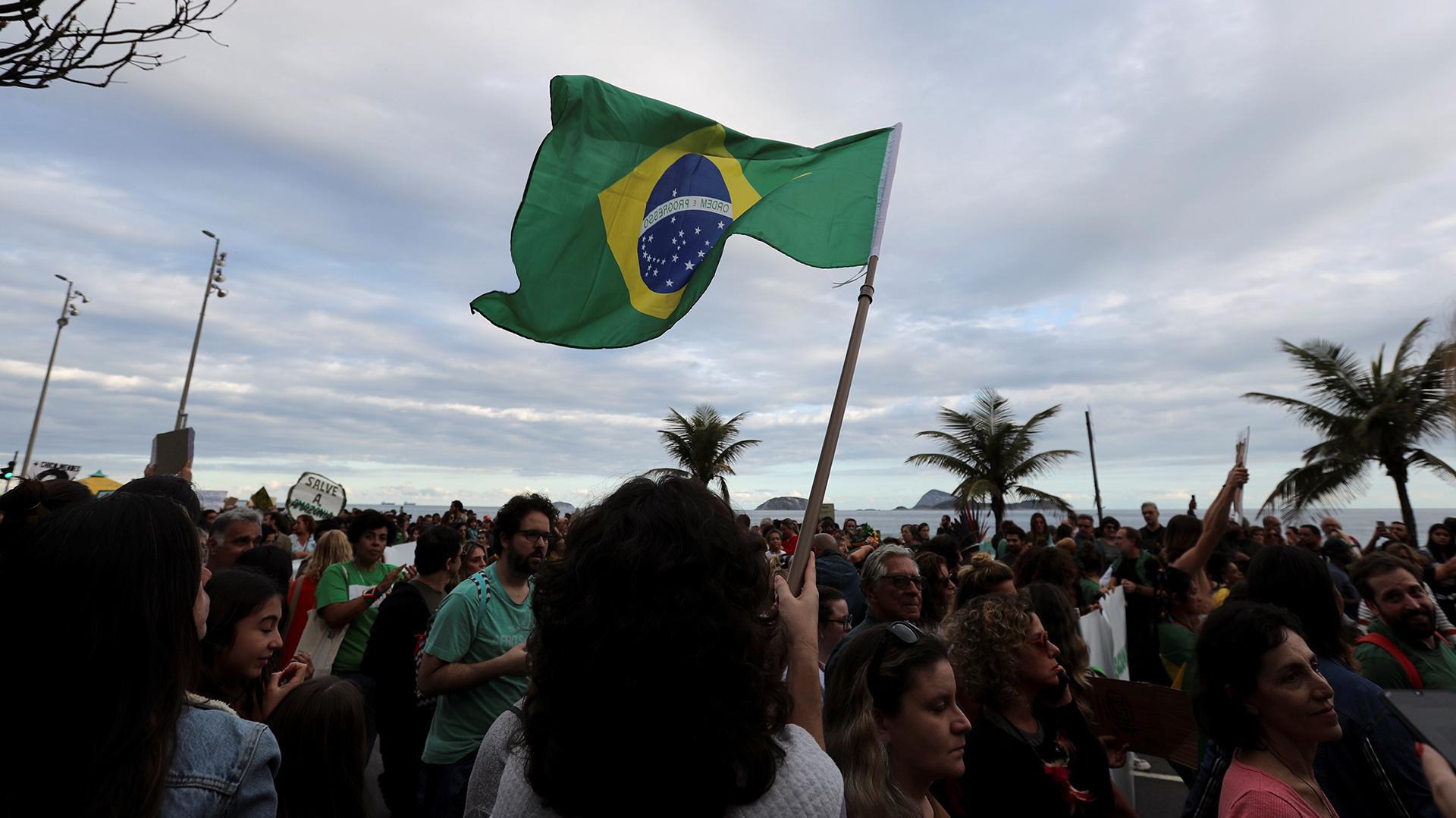 Un asistente sostiene una bandera brasileña durante la manifestación para exigir más protección para la selva amazónica. REUTERS / Sergio Moraes