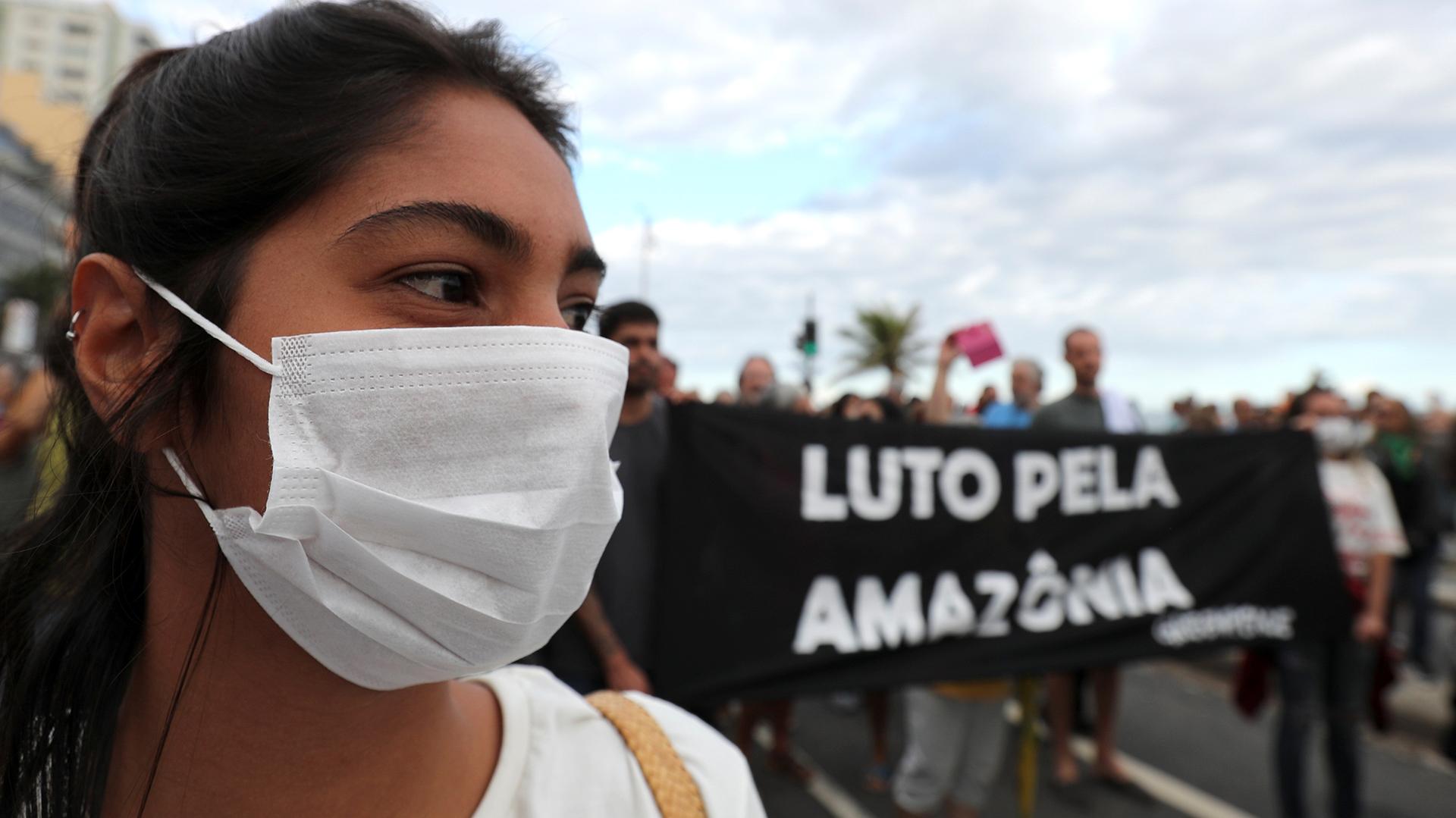 """Una mujer con una máscara asiste a una manifestación para exigir más protección en el Amazonas. El letrero que se encuentra detrás dice """"Luto por la Amazonia"""". REUTERS / Sergio Moraes"""