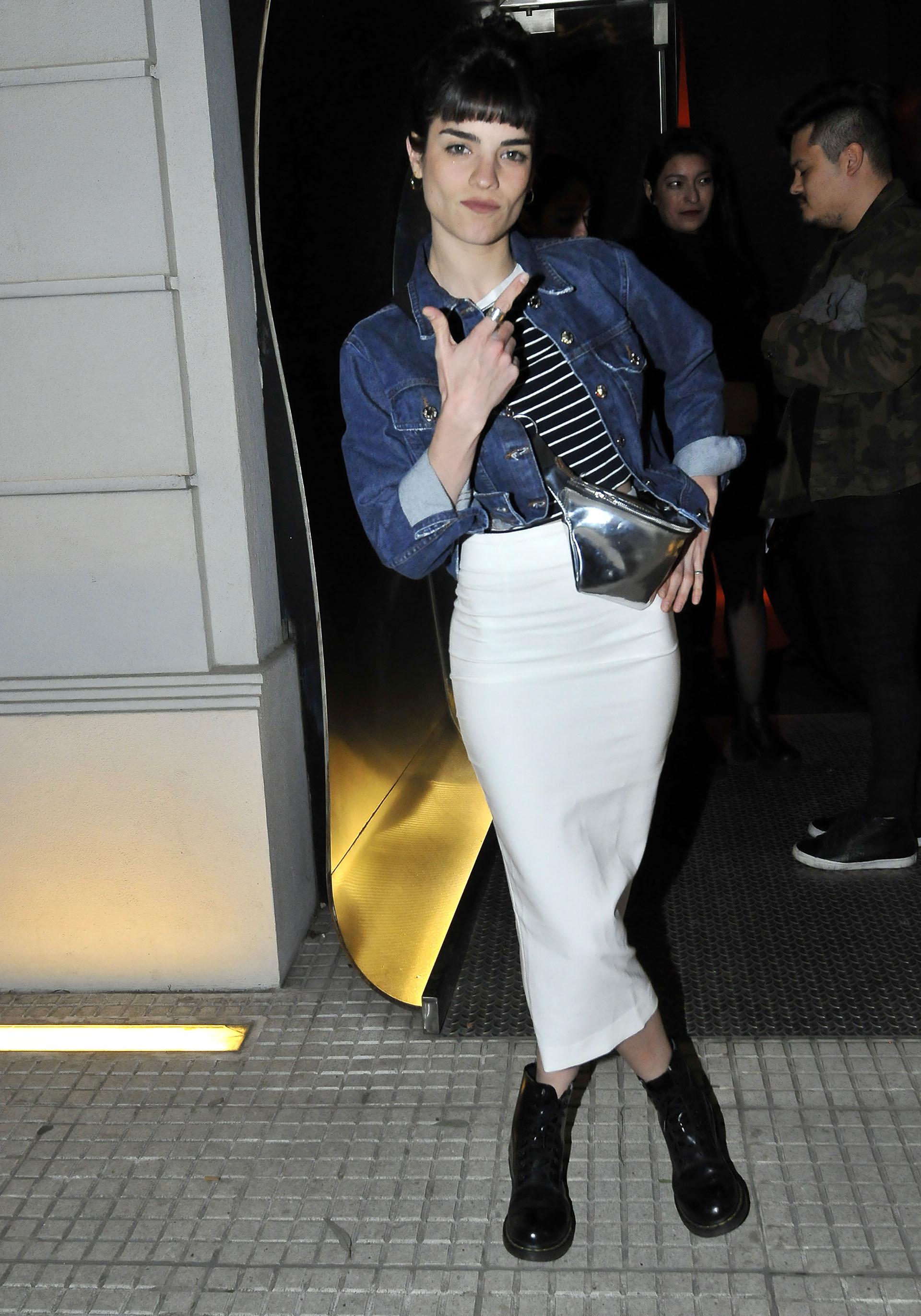 Malena Sánchezdeslumbró conuna campera de jean, remera crop top rayada y falda tubo midi. La actriz de 28 años completó su look con borcegos acharolados y riñonera metalizada
