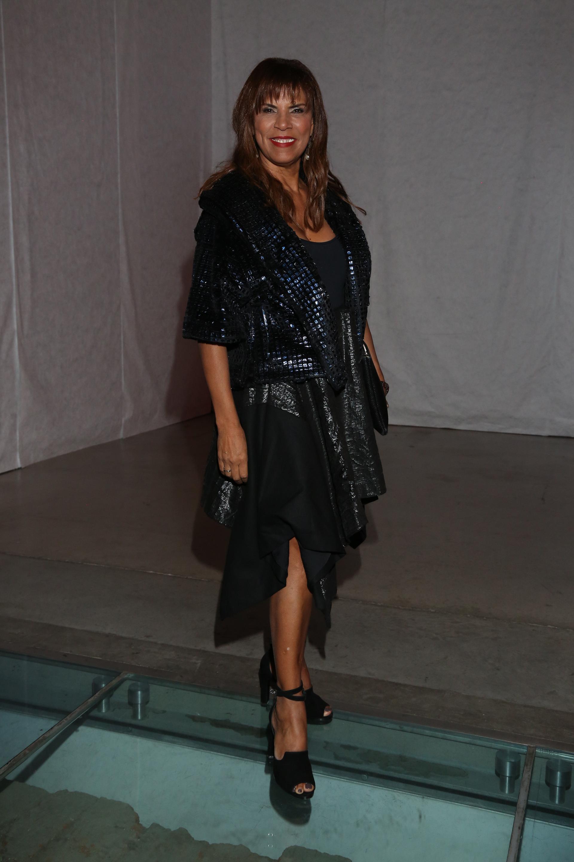 La ex modelo Anamá Ferreira en el desfile de Tramando, vestida por la marca lució un vestido de corte irregular y una chaqueta metálica azul. Completó su look con un sobre negro y sandalias con pulsera regulable