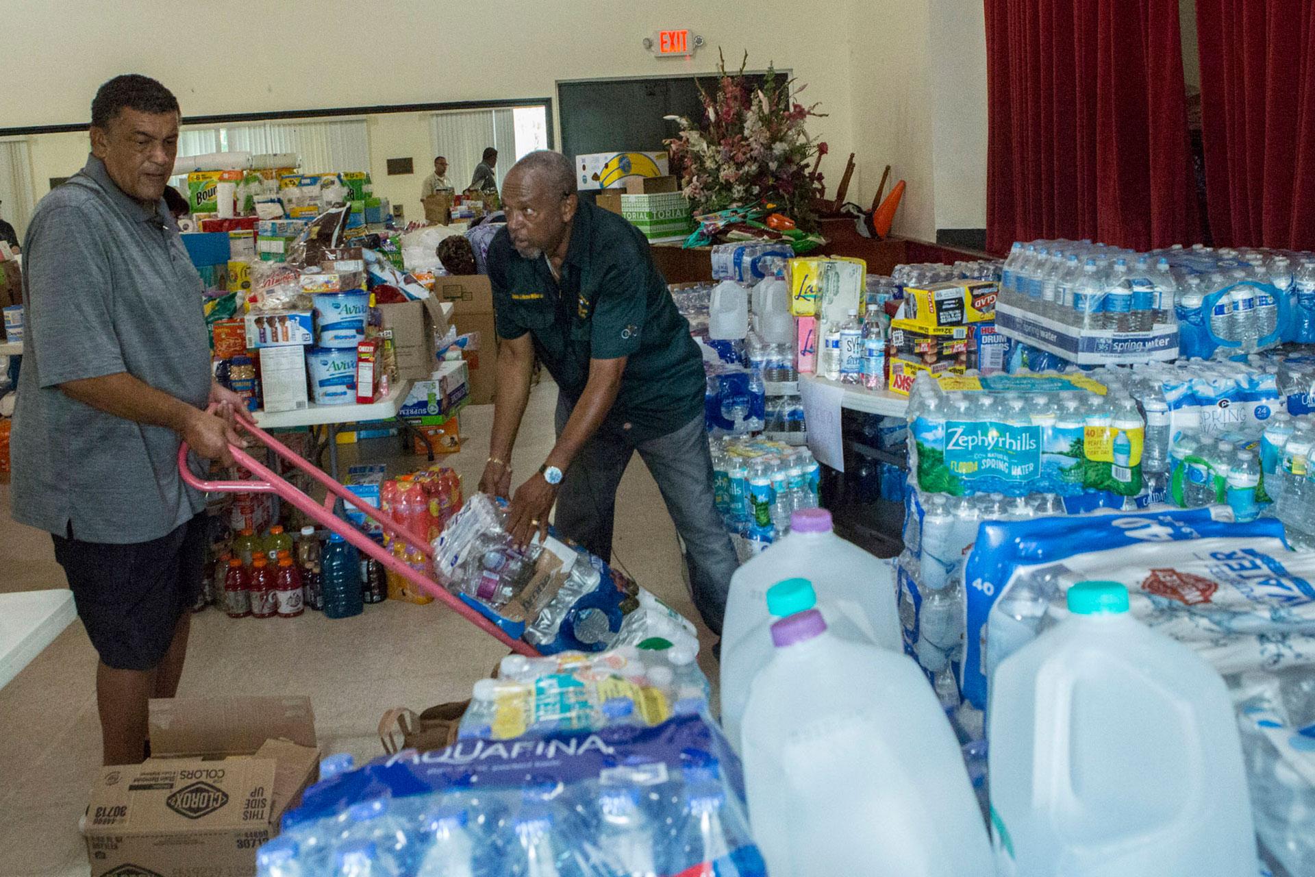 Dos voluntarios juntan agua y artículos de primera necesidad para los afectados por Dorian (AP)