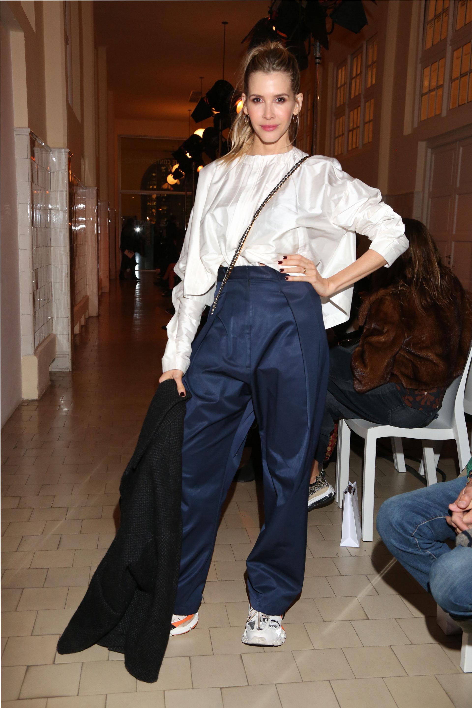 Guillermina Valdes con un diseño de la última colección de JT estuvo en la primera fila del desfile Renaissance en azul y blanco combinado con ugly shoes y tapado negro