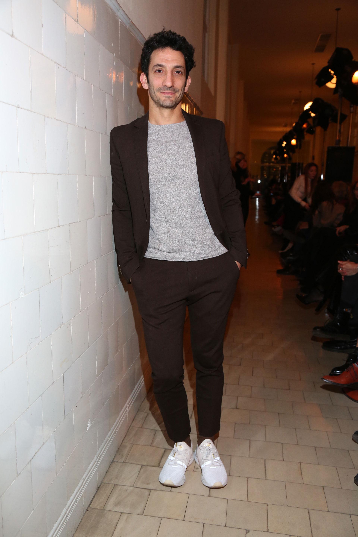 Juan Minujín, uno de los hombres invitados a la primera fila de JT optó por un saco y pantalón en color marrón combinado con remera de algodón gris y zapatillas blancas