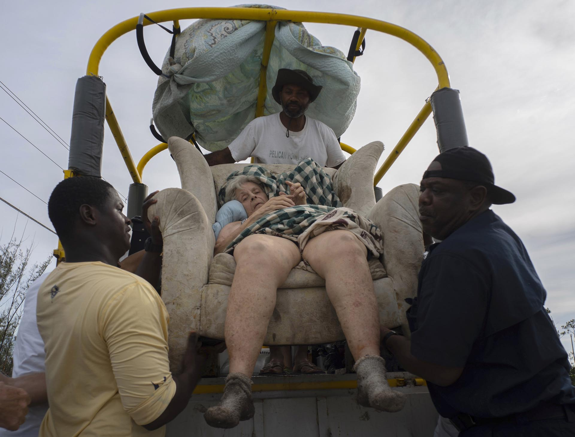 Sentada ensusofá, Virginia Mosvold, de 84 años, es bajada de un camión por voluntarios después de ser rescatada de su casa inundada en la granja de Ol 'Freetown Farm después del huracán Dorian antes de ser llevada al hospital en las afueras de Freeport, Bahamas el m iércoles 4 de septiembre de 2019