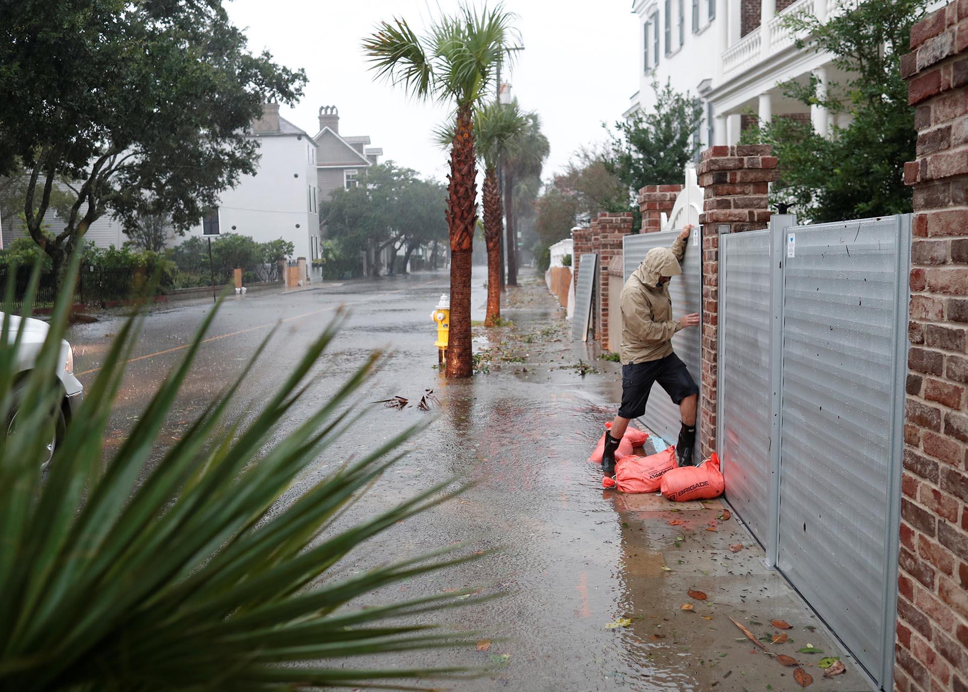 Brys Stephens intenta instalar una puerta de metal enSouth Battery mientras el huracán Dorian selanza sobre Charleston, Carolina del Sur