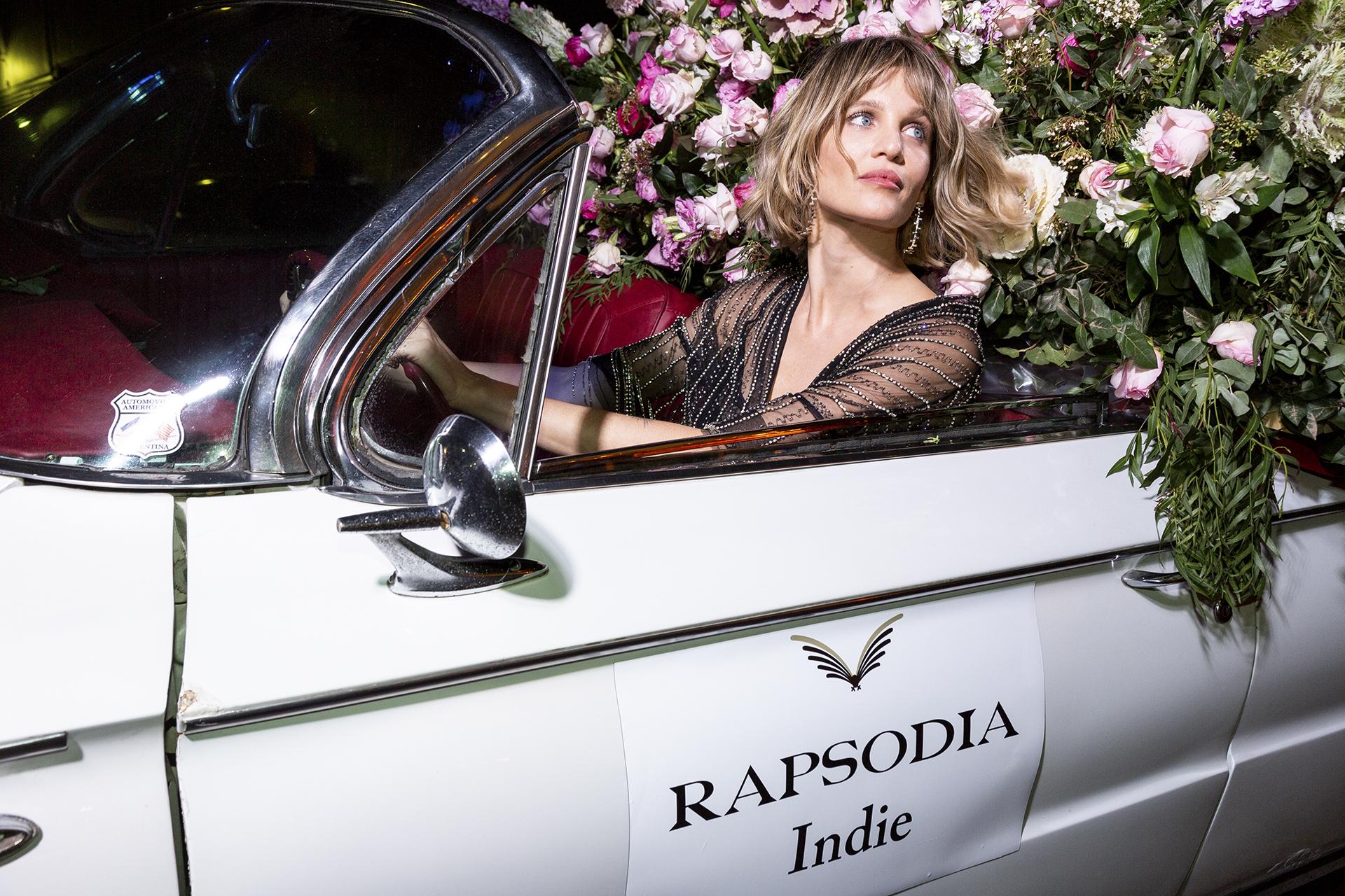 Liz Solari rodeada de flores en el auto de Rapsodia Indie