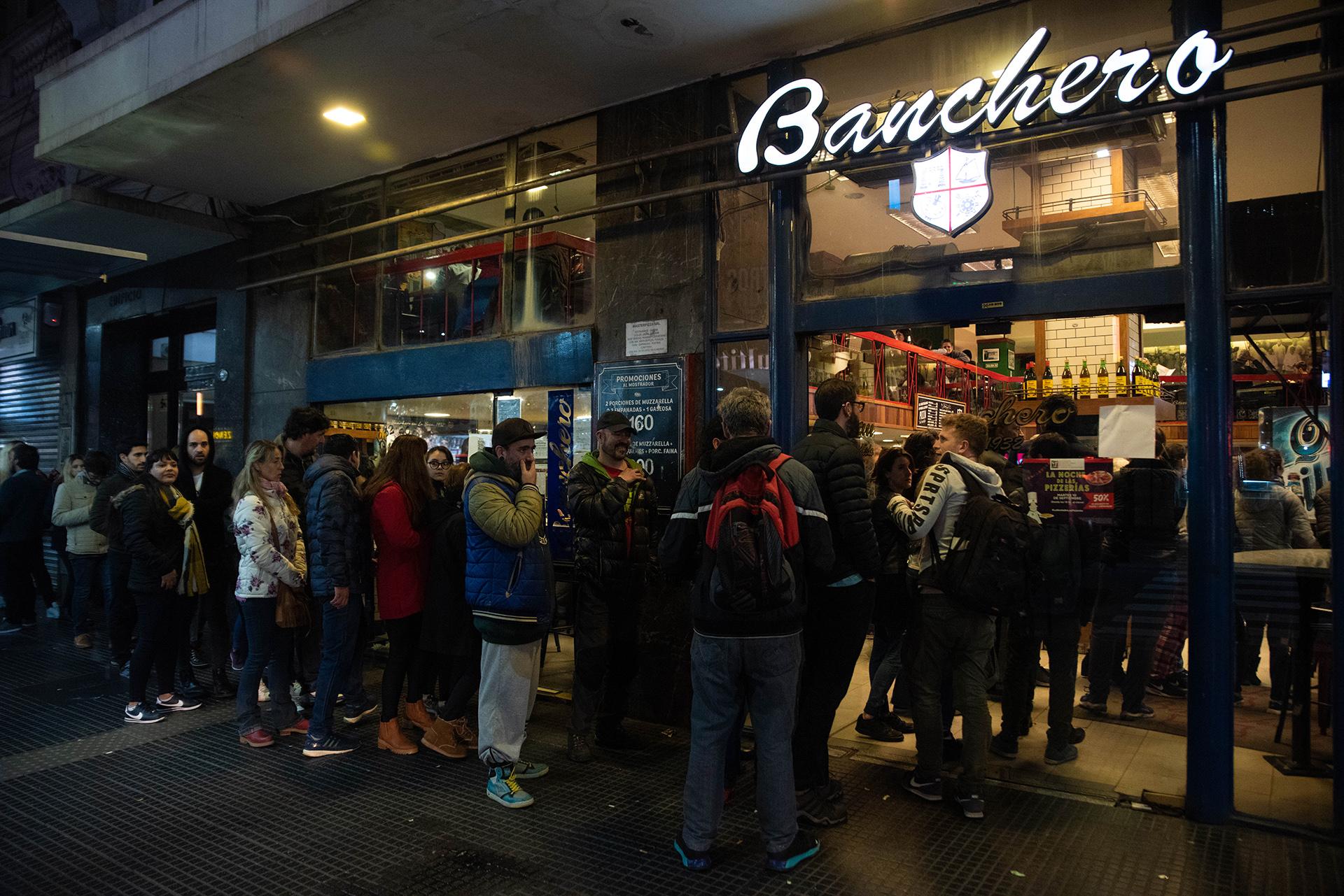 Comensales ansiosos haciendo fila en la puerta de Banchero esperando por una mesa en el salón de doble piso en la esquina de Avenida Corrientes y Talcahuano