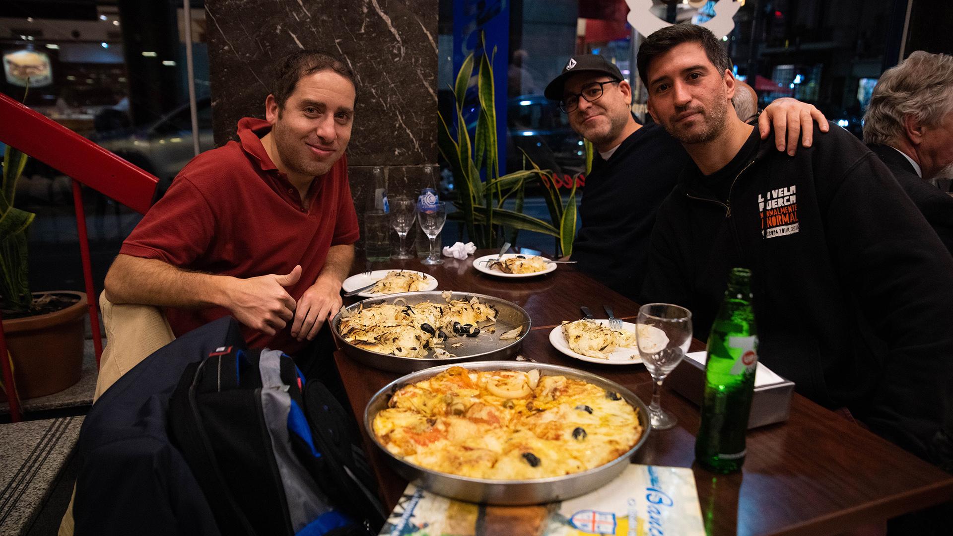 Amigos en Banchero disfrutando una fugazzetta y otra napolitana, dos clásicas de la tradicional pizzería de la Avenida Corrientes