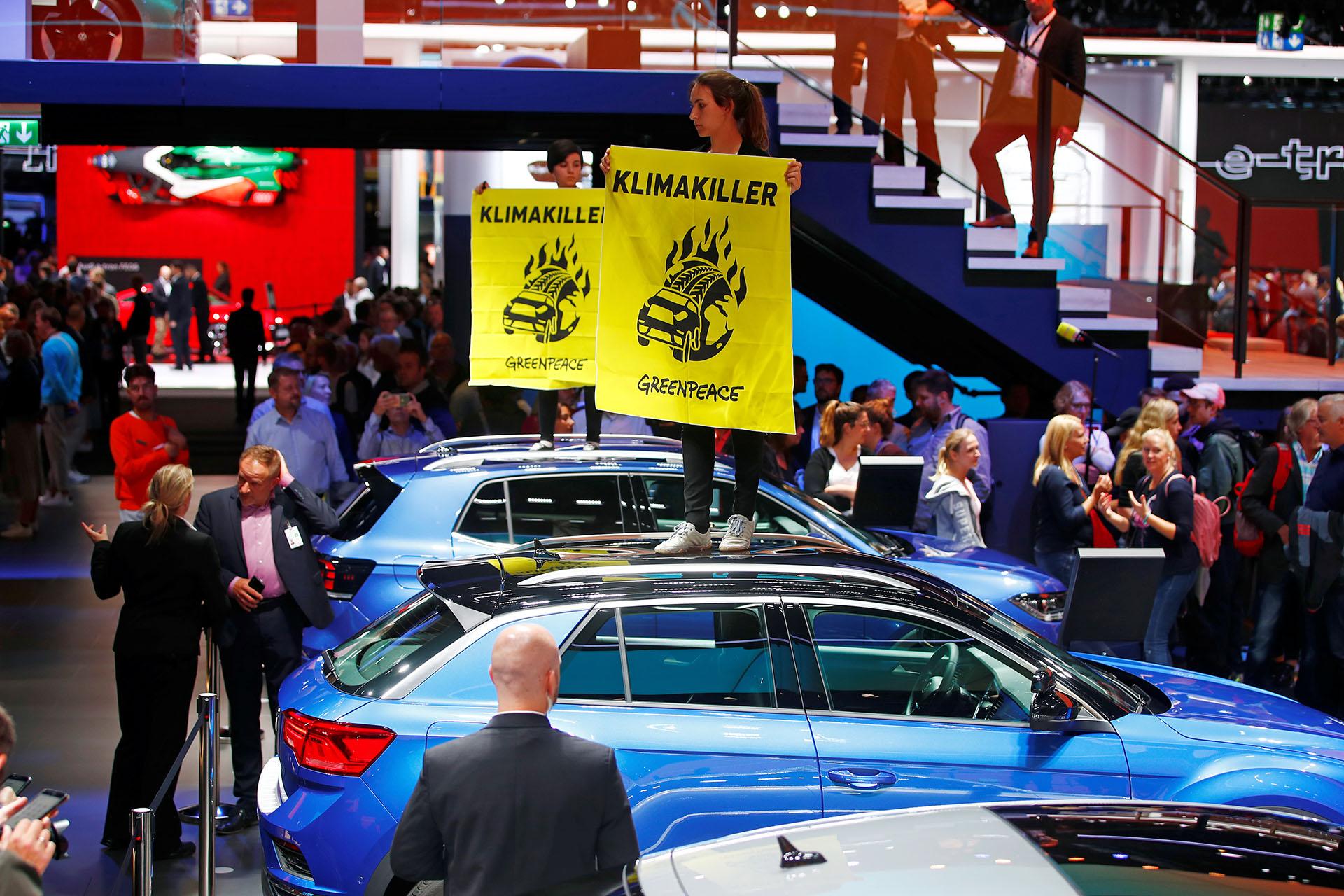 """Mientras Merkel se dirigía a la feria, un pequeño grupo de manifestantes en las afueras de la misma exhortaban a """"proteger el clima en lugar de los todoterrenos"""" en pancartas, presagiando una protesta más grande programada para el sábado"""
