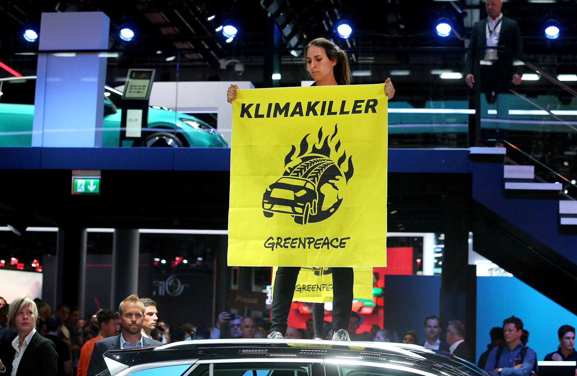 Una activista de Greenpeace se sube a un coche exhibido mientras protesta contra el calentamiento global durante la visita de la canciller alemana Angela Merkel al Salón Internacional del Automóvil de Frankfurt