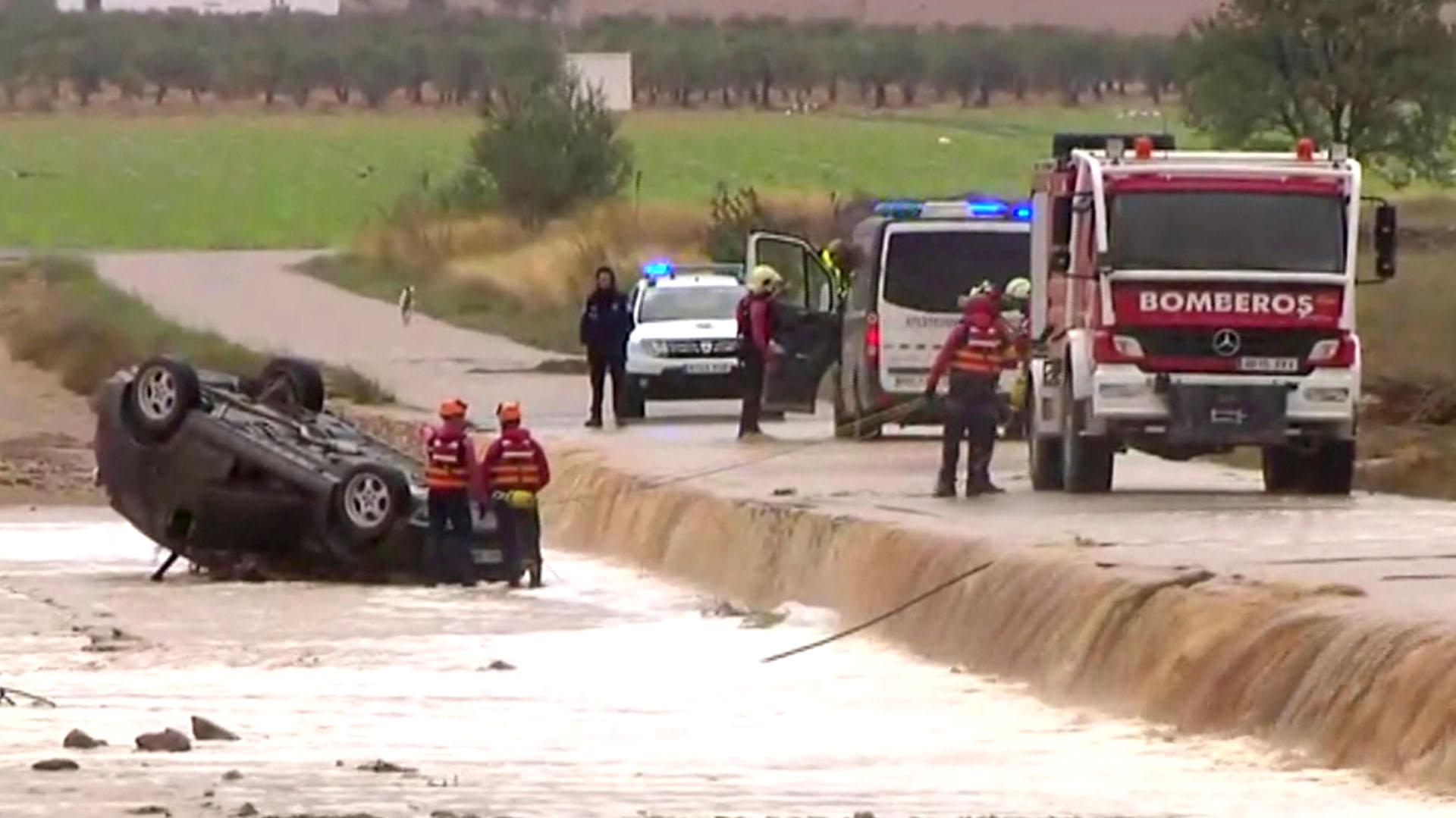 Trabajadores de rescate junto a un auto volcado donde una pareja de ancianos murió tras las fuertes inundaciones en Albacete (Atlas/Reuters TV vía REUTERS)