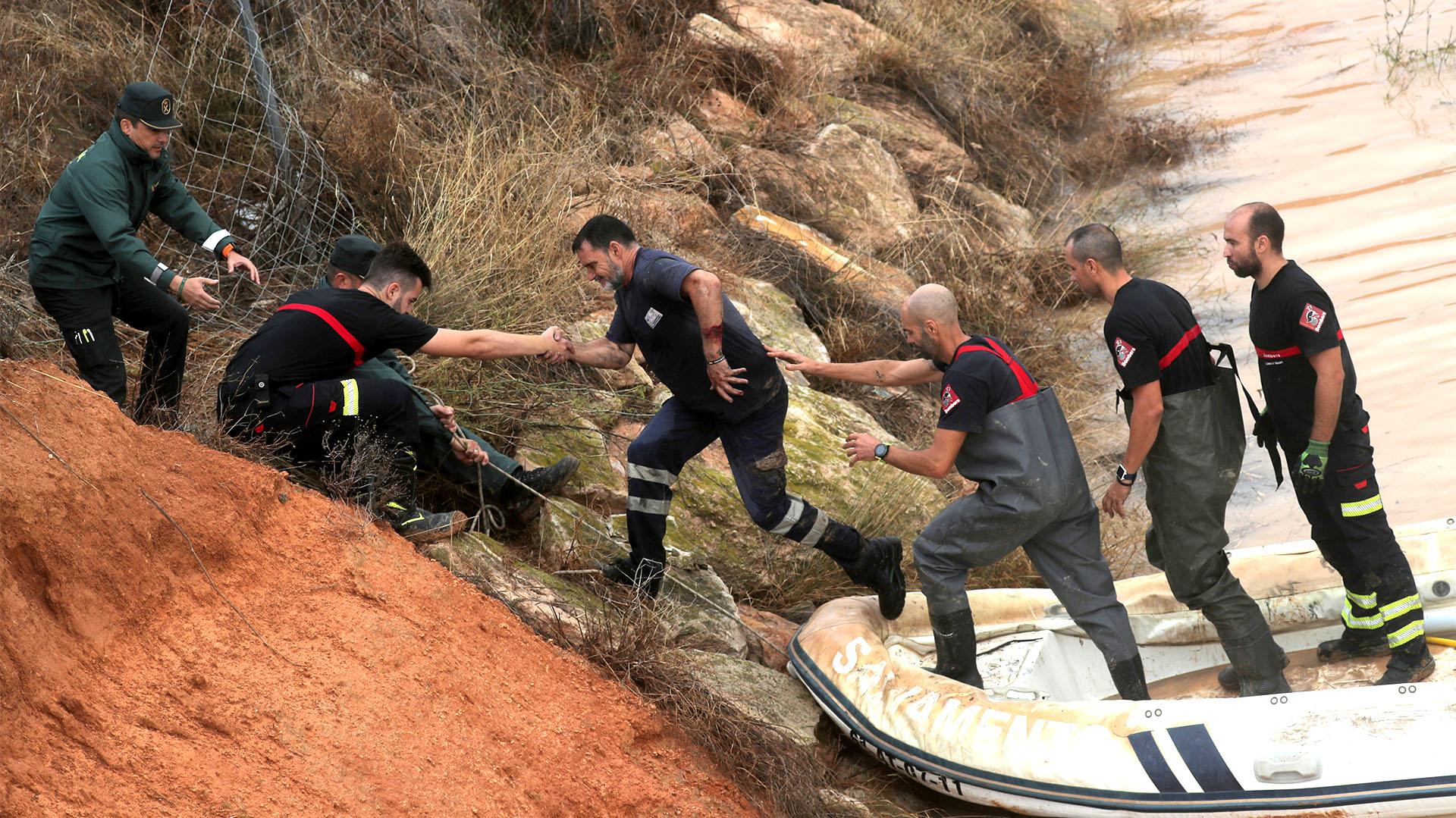 Socorristas ayudan a un hombre que quedó varado dentro de un túnel inundado tras las fuertes lluvias en Pilar de la Horadada (REUTERS/Sergio Pérez)