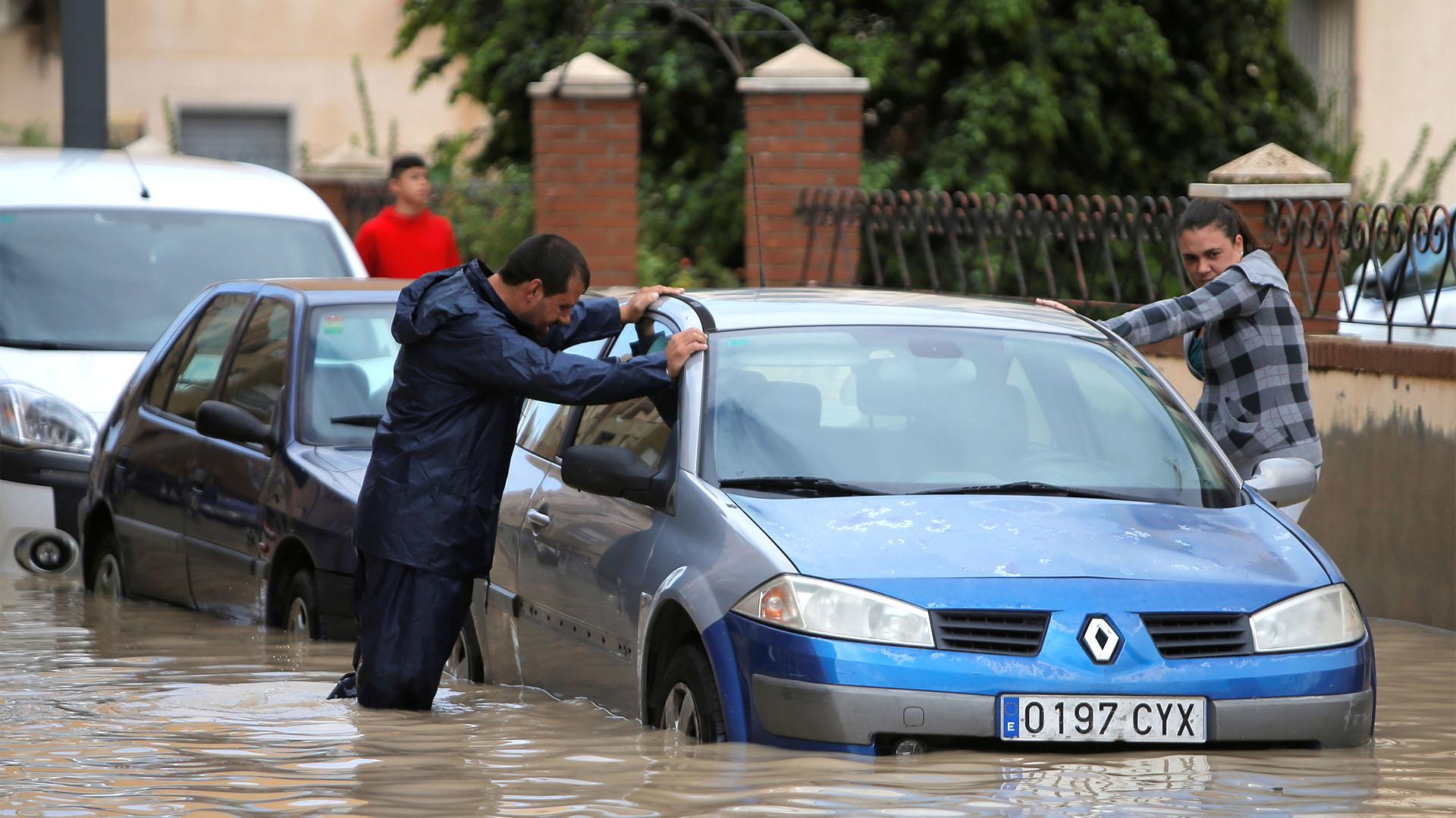 Dos personas junto a un auto parcialmente sumergido tras lluvias torrenciales en Orihuela (REUTERS/Jon Nazca)
