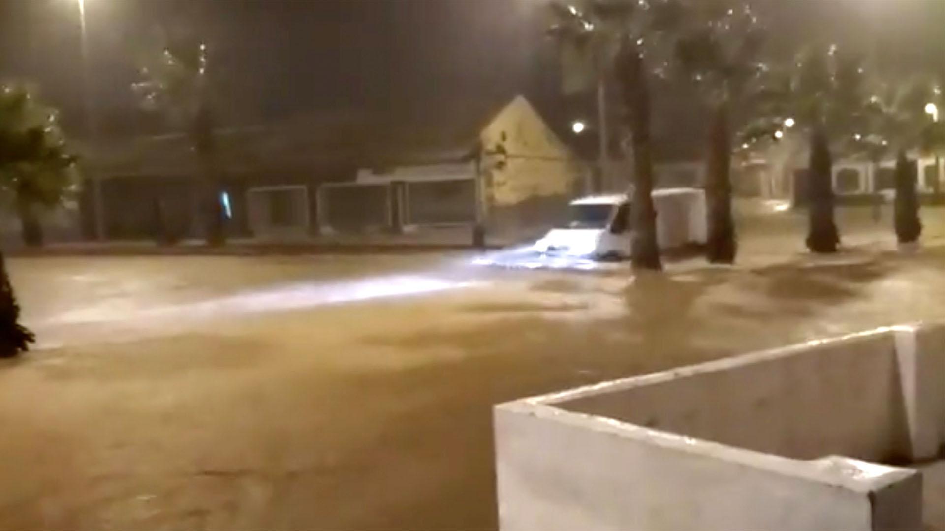Un vehículo pasa por una calle inundada en El Algar, España, en esta imagen tomada de un video de redes sociales (LUCAS GARCIA via REUTERS)