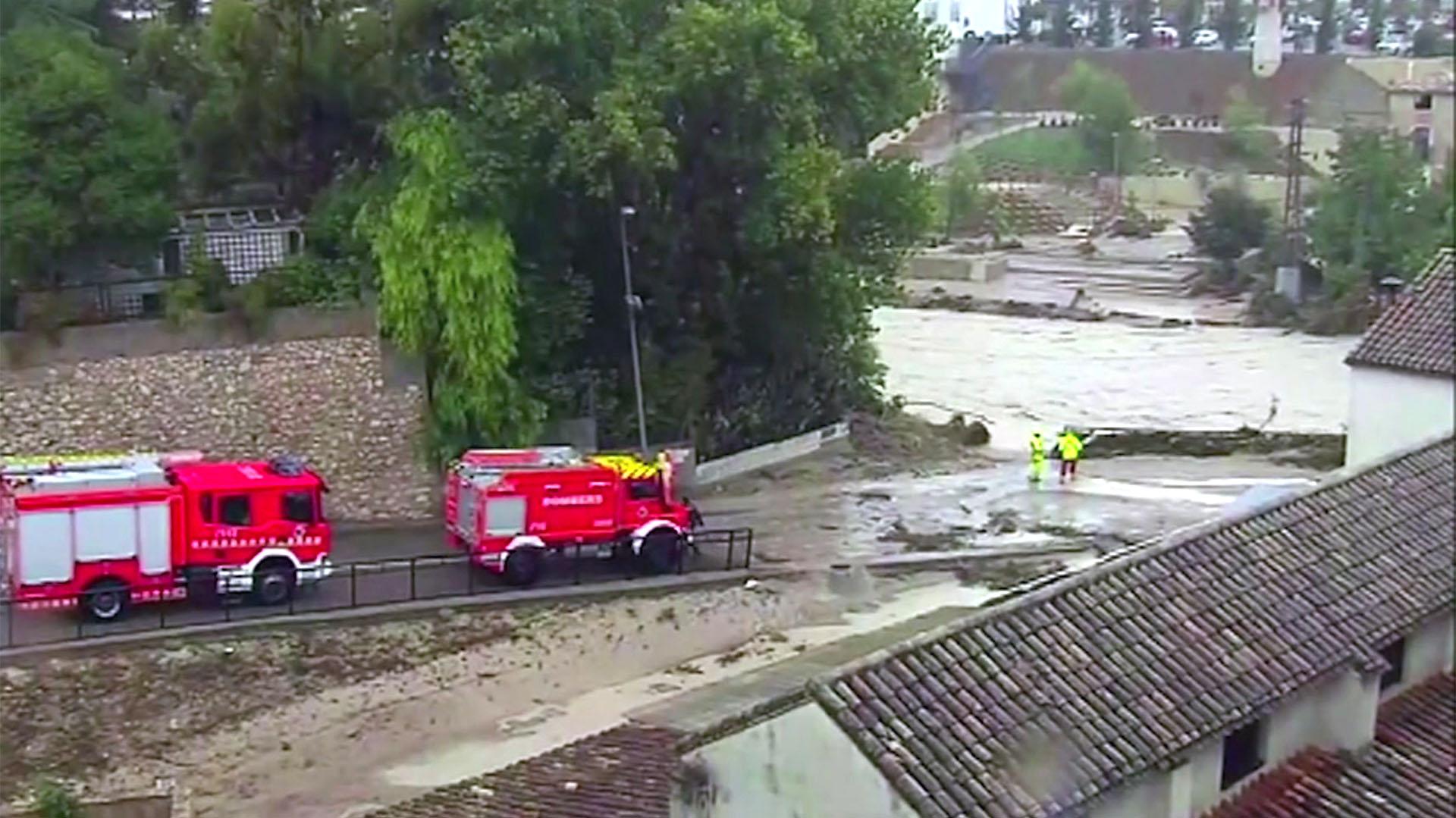 Camiones de bomberos conducen por un río inundado, en Ontiyente, España, el jueves 12 de septiembre (Atlas vía AP)