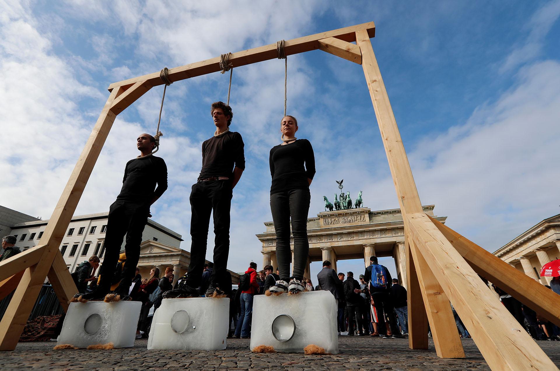 Activistas de pie sobre bloques de hielo bajo una horca improvisada en el marco de la Huelga Climática Global en Berlín (REUTERS/Fabrizio Bensch)