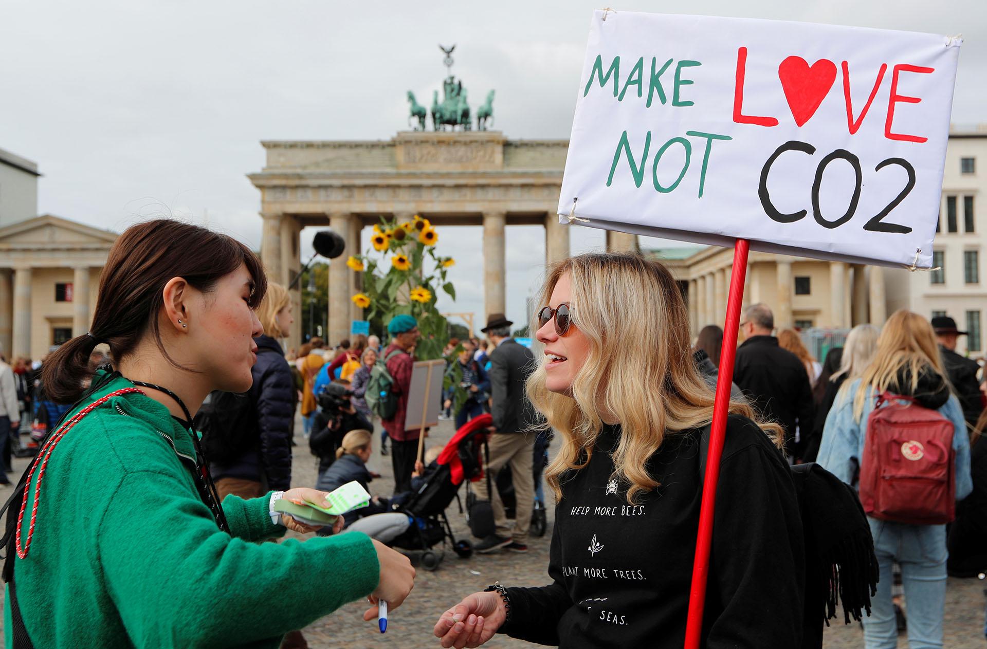 """""""Hagamos el amor, no dióxido de carbono"""", dice el cartel sostenido por una joven alemana(REUTERS/Fabrizio Bensch)"""