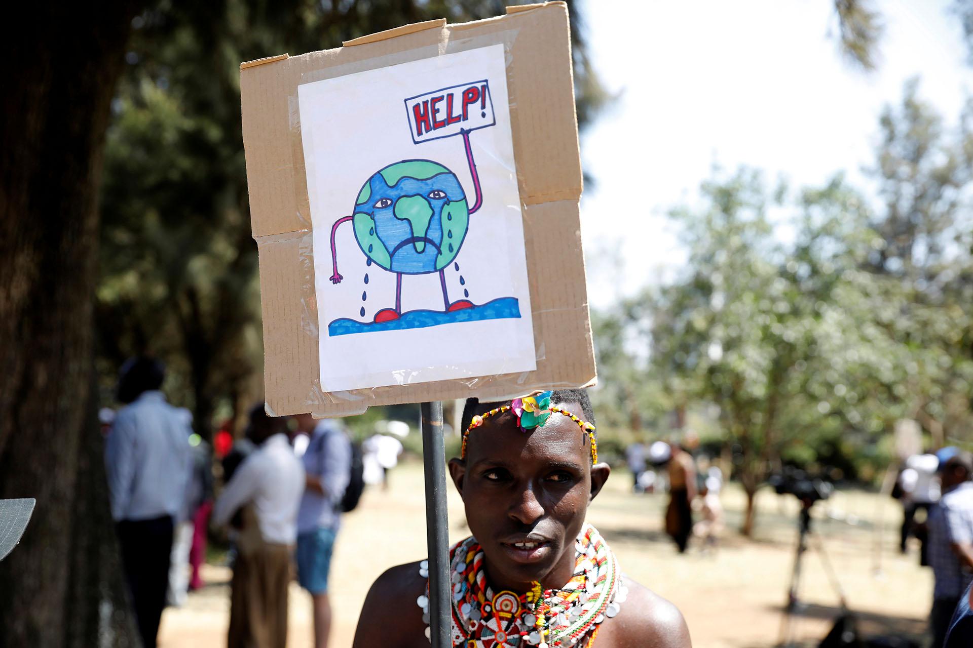 Un activista ambiental vestido con ropa tradicional sostiene un letrero en la huelga climática global celebrada en Kenia (REUTERS/Baz Ratner)