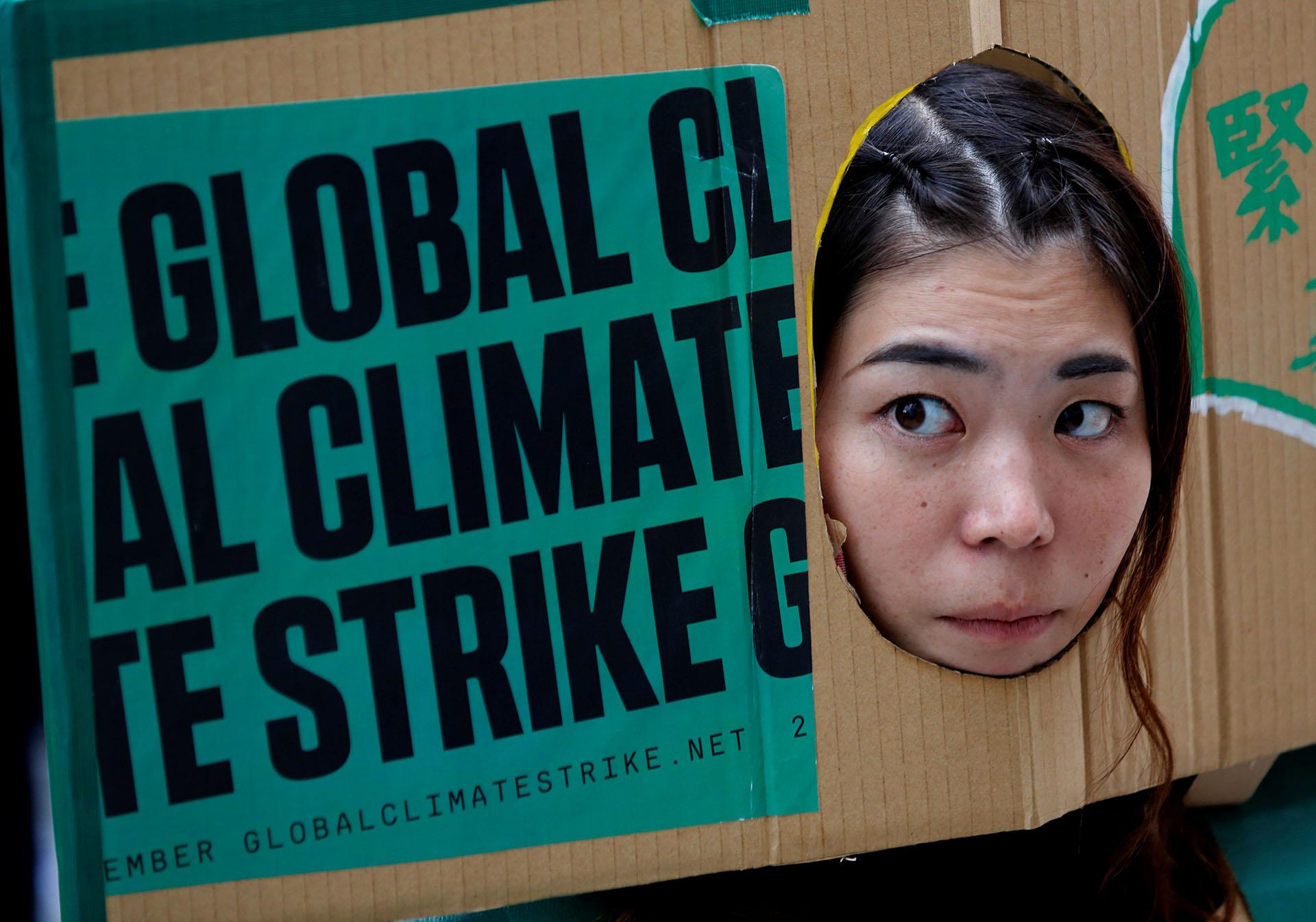 Una mujer asoma su rostro a través de una pancarta en la huelga climática celebrada en Tokio, Japón (REUTERS/Kim Kyung-Hoon)