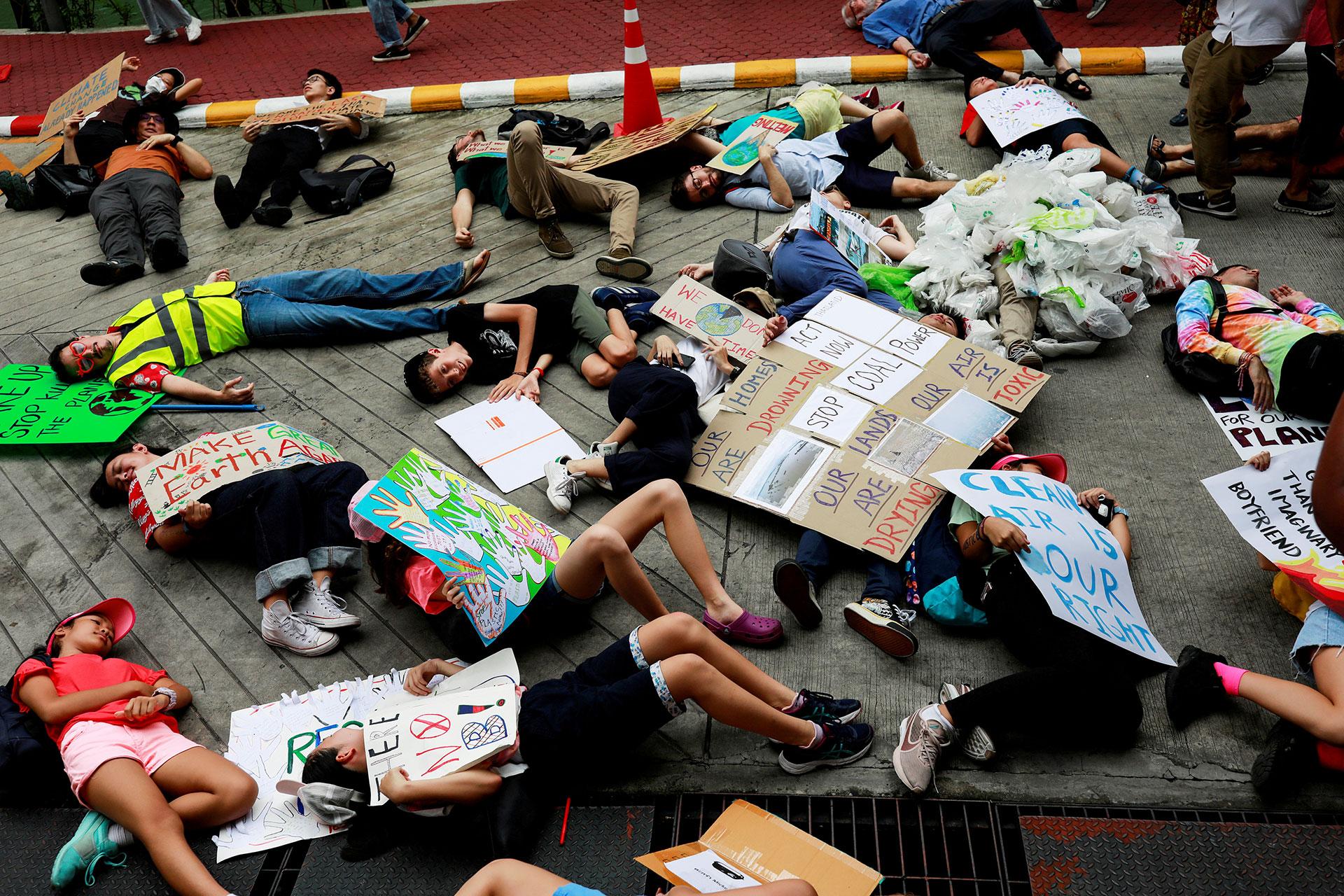 Jóvenes se hacen los muertos en la huelga climática global cerca de la oficina del Ministerio de Recursos Naturales y Medio Ambiente en Bangkok, Tailandia (REUTERS/Soe Zeya Tun)