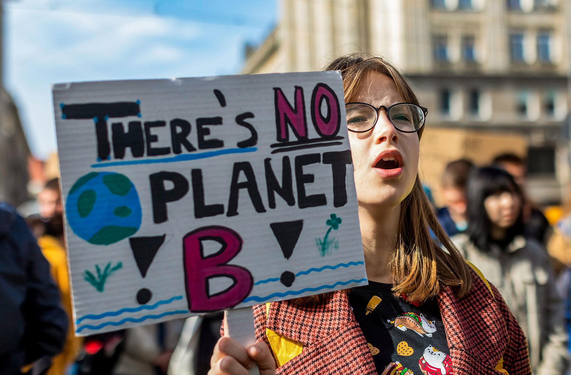 """Una joven manifestante sostiene una pancarta con la leyenda """"No hay planeta B""""en Varsovia (Foto de Wojtek RADWANSKI / AFP)"""