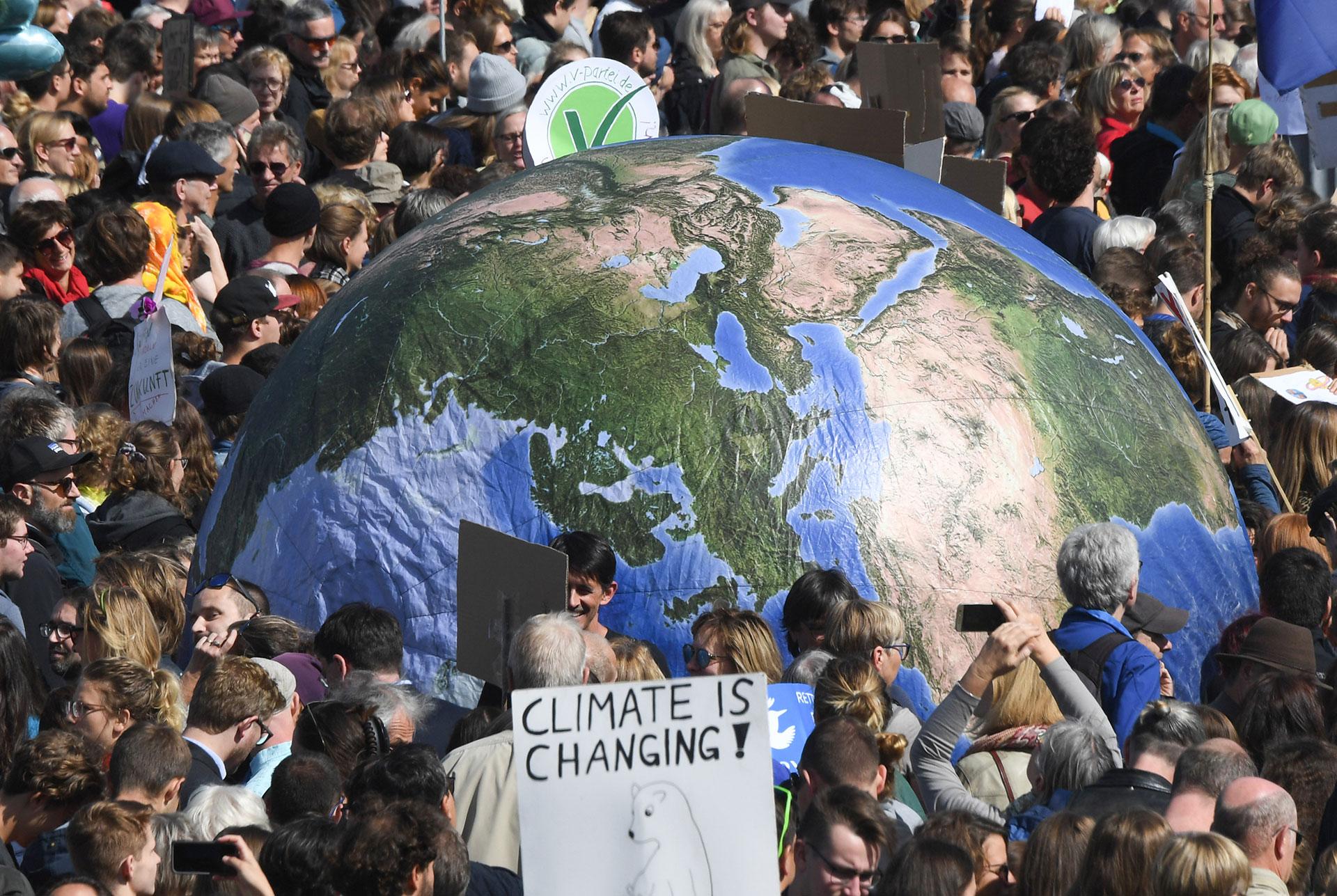 """Jóvenes con un globo terráqueo participan en la manifestación """"Viernes por el Futuro"""" en Munich, al sur de Alemania (Foto de Christof STACHE / AFP)"""