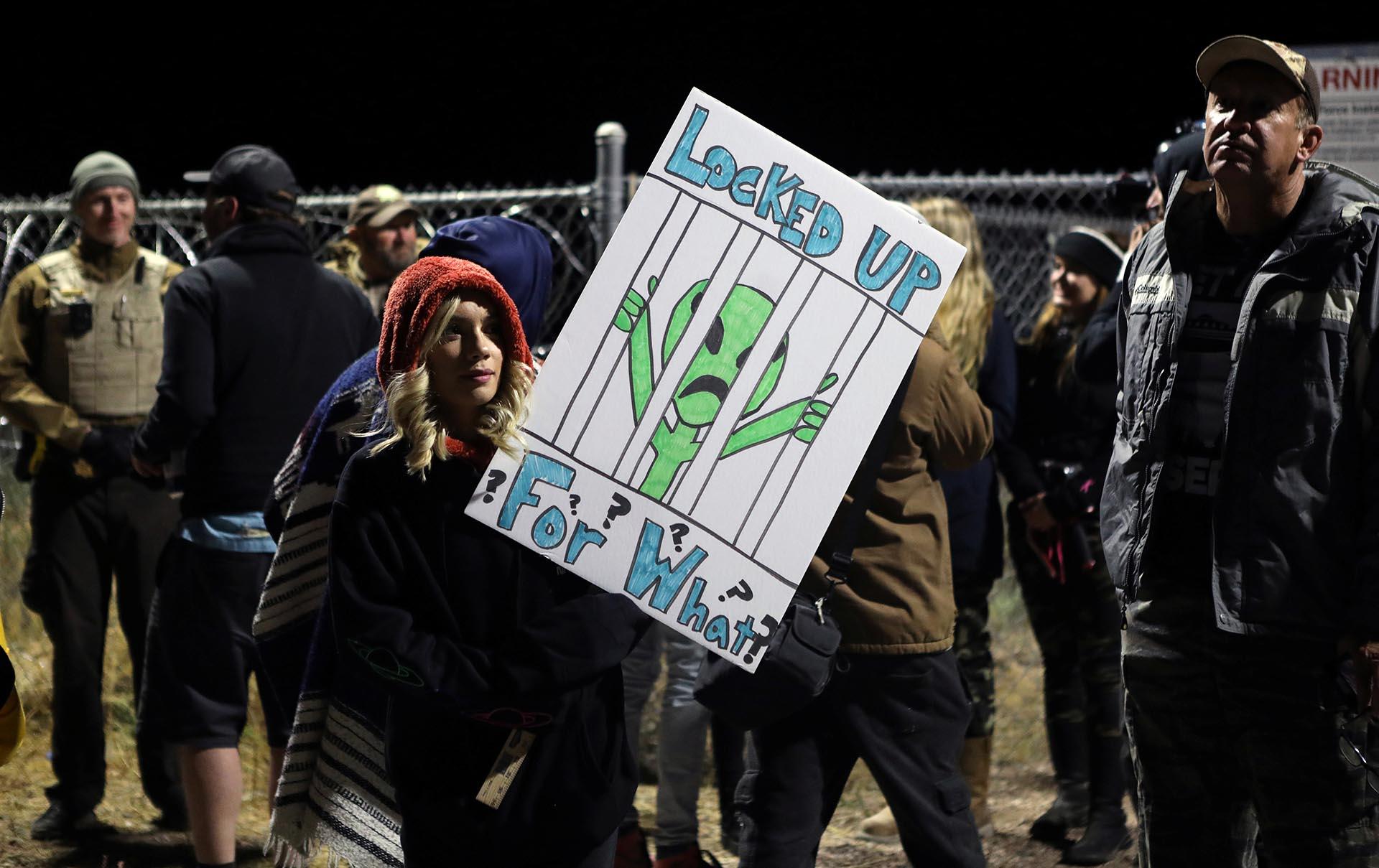 """Una mujer lleva un letrero que dice """"Encerrados, ¿por qué?"""" frente a una puerta del Área 51, una base militar secreta de los EEUU que los entusiastas de los OVNIS creen que guarda secretos del gobierno sobre extraterrestres, en Rachel, Nevada, EEUU (REUTERS/Jim Urquhart)"""