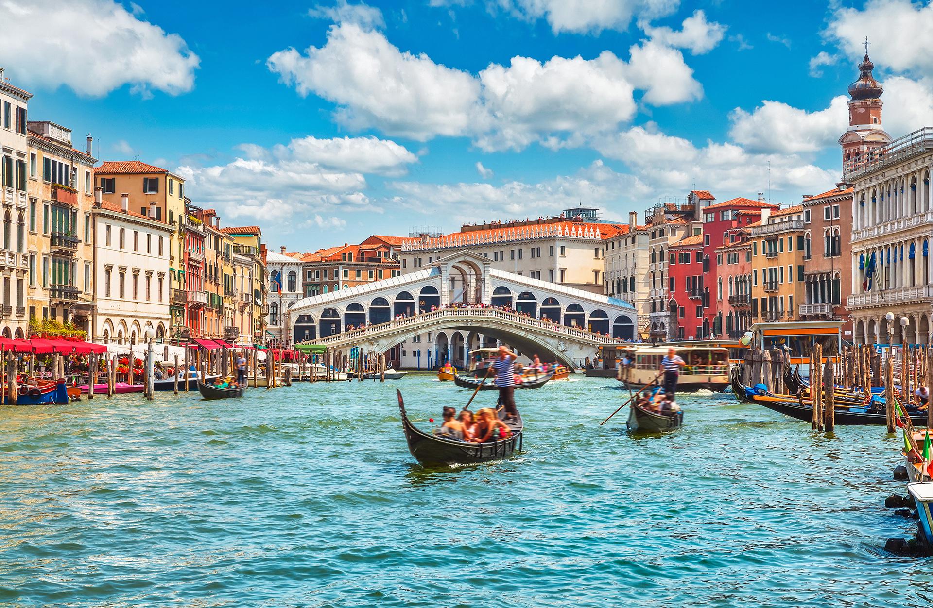 Recorridas en góndolas por las calles de Venecia. La llegada a la mítica Plaza de San Marcos y el puente Rialto, uno de los más famosos de toda la ciudad. Los gondoleros reciben a los turistas con sus trajes típicos y sombreros y llevan a recorrer Venecia por los canales