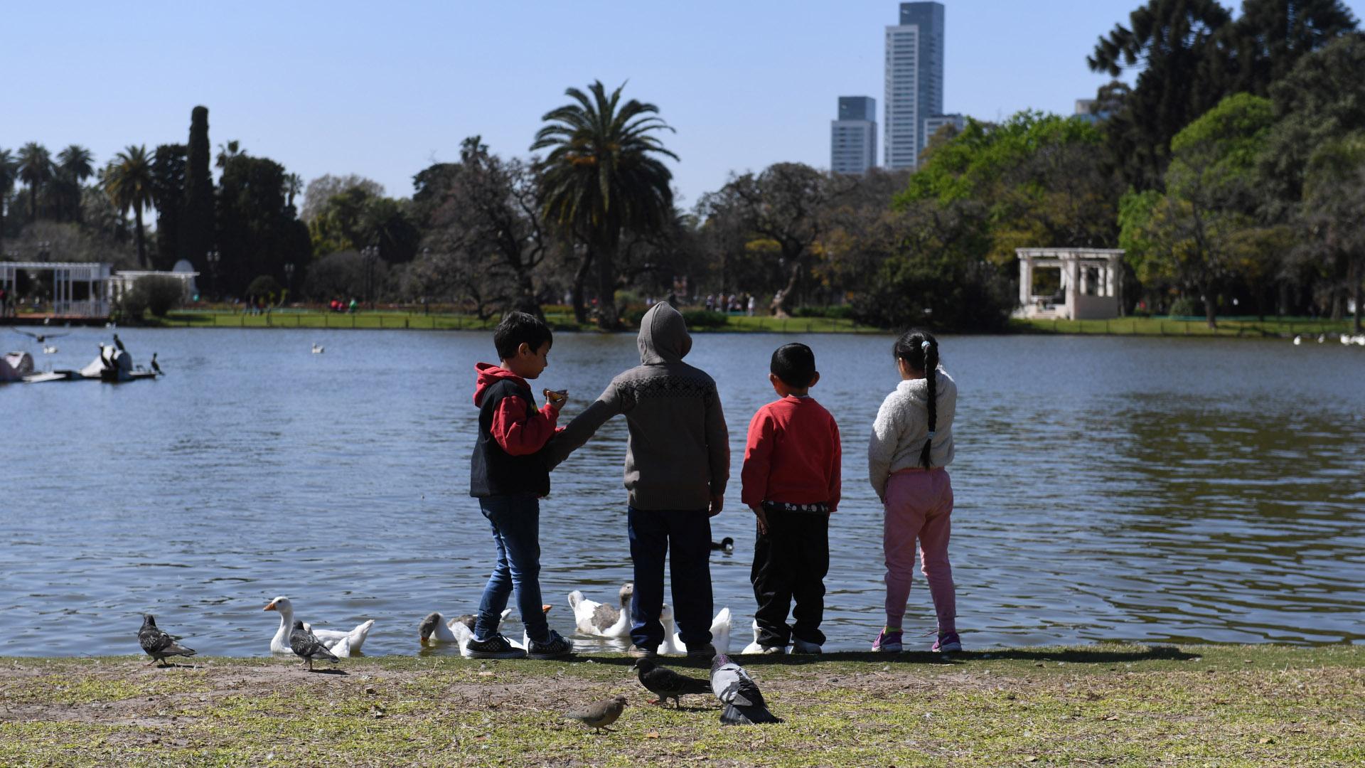 Los más chiquitos de la familia se entretienen alimentando a los patos que están en el lago del Rosedal de Palermo