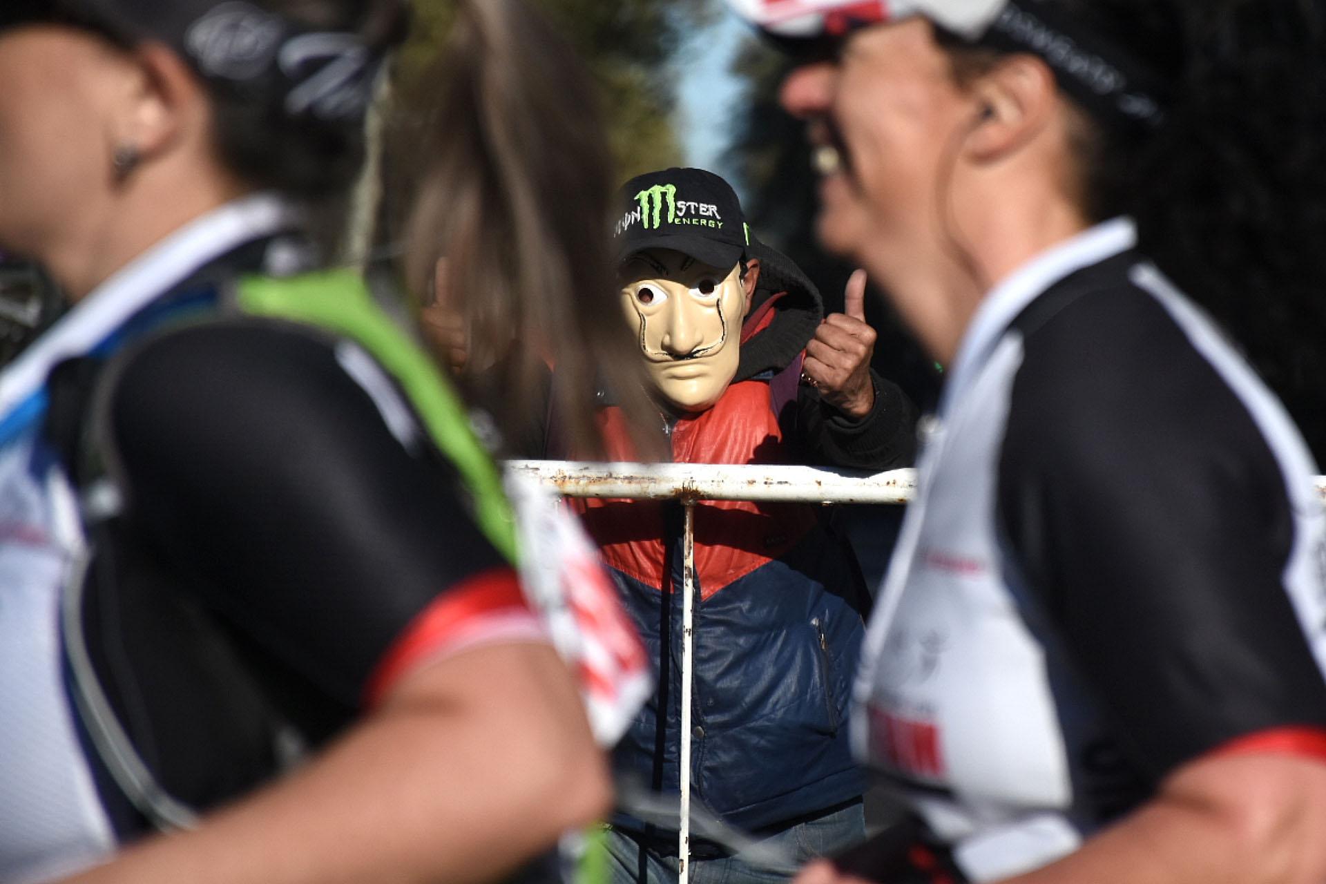 El simpatizante con su máscara, a uno de los lados de la valla
