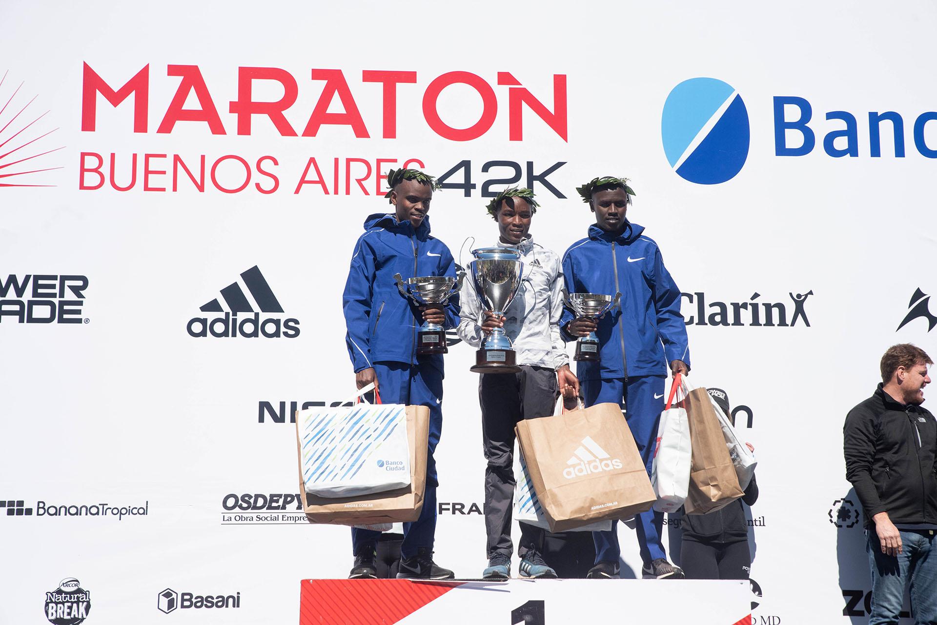 Los tres integrantes del podio, con sus trofeos y regalos en las manos