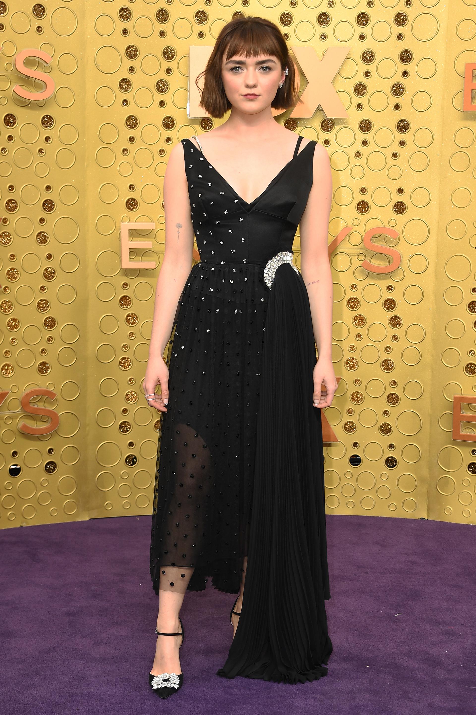 Maisie Williams apostó a un diseño de corte midi con un gran escote V y varias texturas sobre el vestido: plisado, tul y bordado. Completó su look con stilettos de Manolo Blahnik