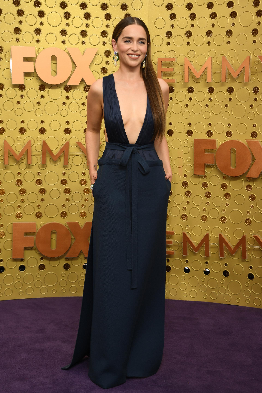 Emilia Clarkeby Valentino. La actriz lució un vestido con gran escote V plisado y lazo en la cintura en color petróleo y completó su look con maxi aros joya