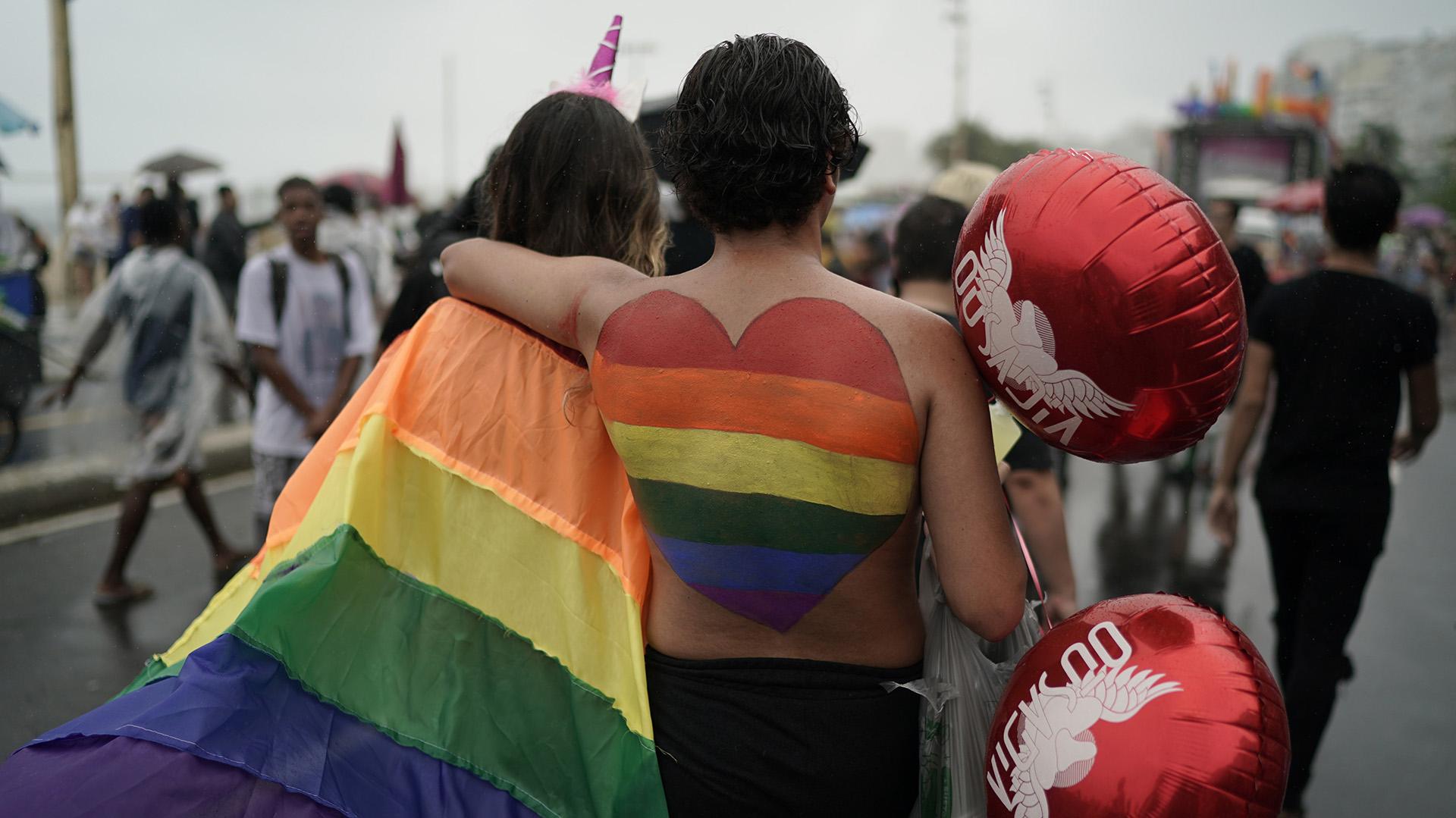 Las personas asisten al desfile anual del orgullo gay a lo largo de la playa de Copacabana. (Foto AP / Leo Correa)