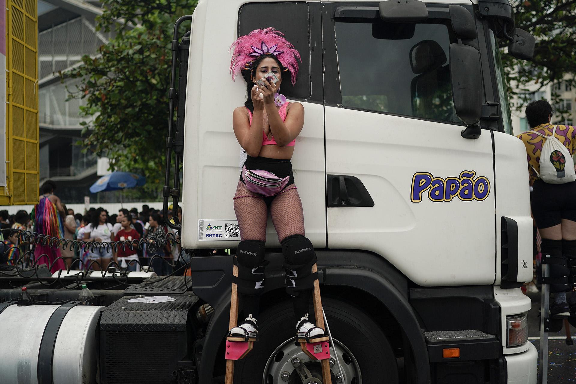 Una mujer en zancos retoca su maquillaje durante el desfile. (Foto AP / Leo Correa)