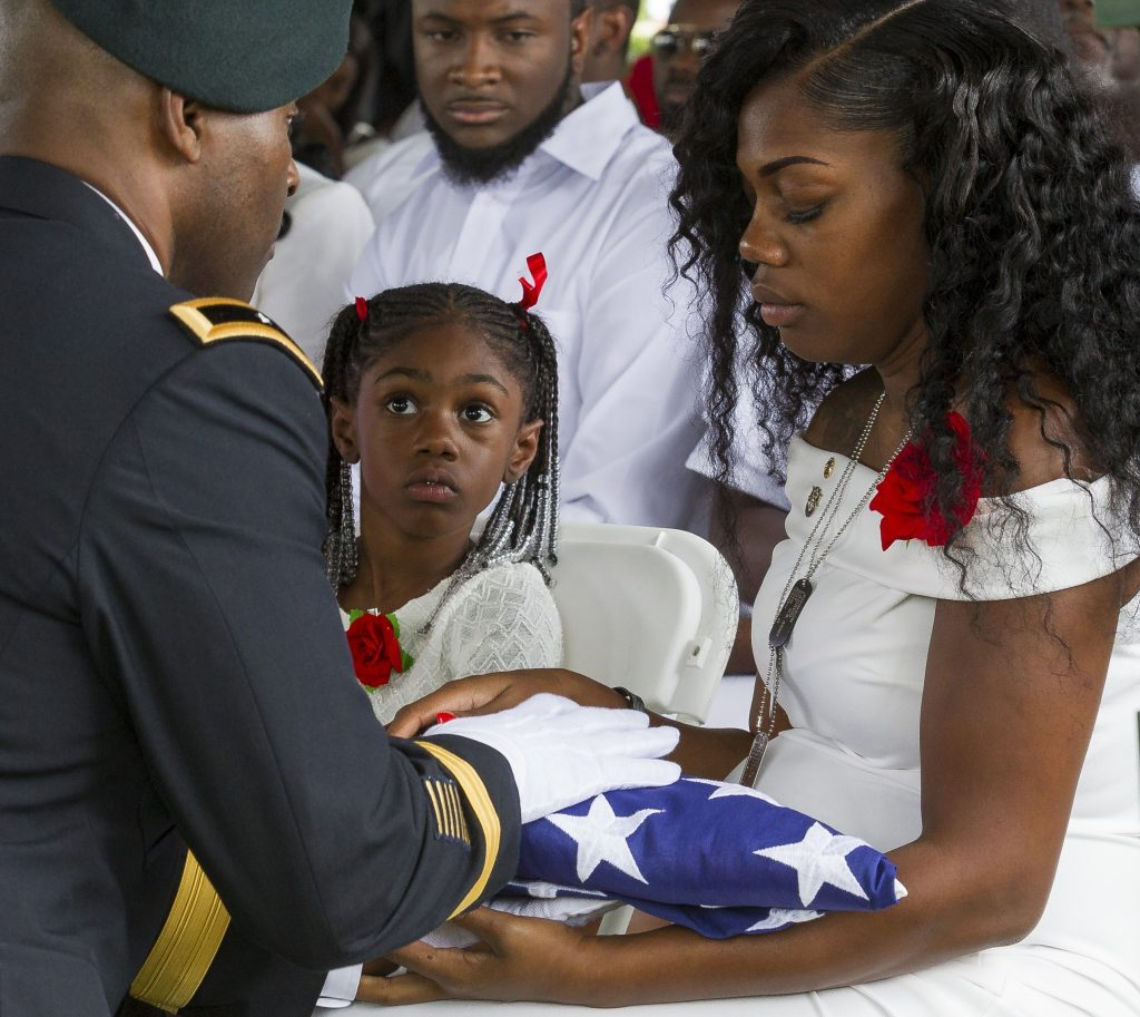 Myeshia Johnson is presented with the U.S. flag that was draped over the casket of her husband, Sgt. La David Johnson, during his burial service at Fred Hunter's Hollywood Memorial Gardens in Hollywood, Fla., on Saturday, Oct. 21, 2017. [Matias J. Ocner | Miami Herald via AP]