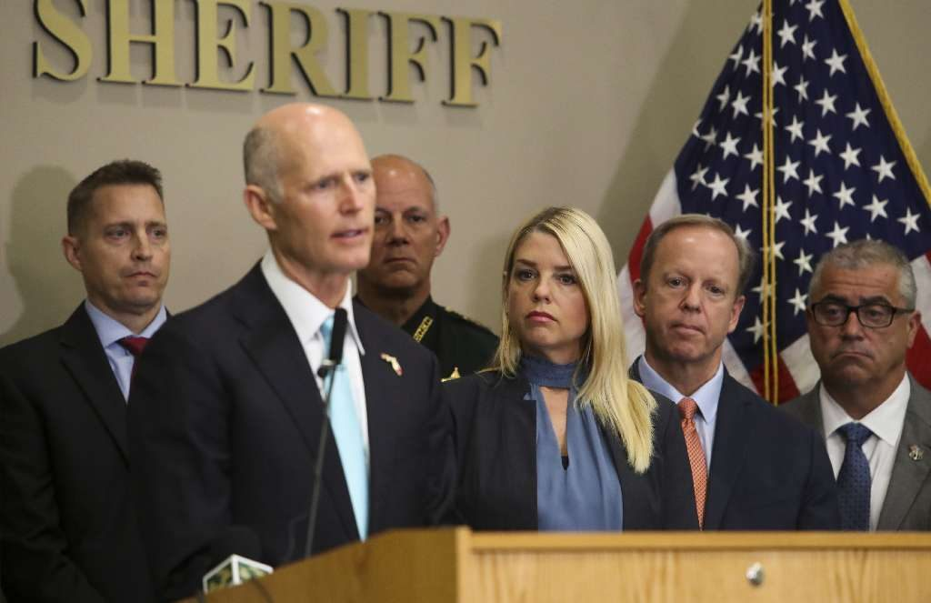 Florida Attorney General Pam Bondi (right) listens to Gov. Rick Scott (podium) speak to the media at the Hillsborough County Sheriffs Office to discuss his plans to keep Florida's schools safe after the Feb. 14 Parkland mass shooting. Hillsborough School Superintendent Jeff Eakins is in back left of the photo. [MONICA HERNDON | Times]