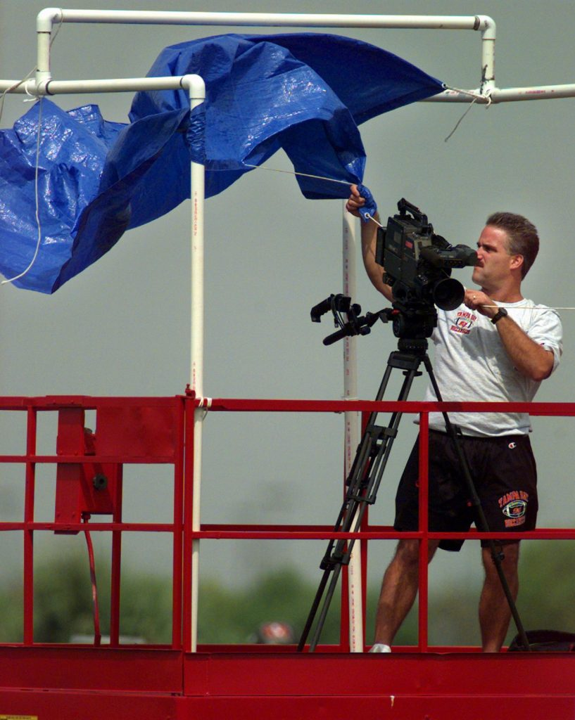 In this 1997 file photo, Bucs video director Dave Levy holds down a cover as the wind whips through One Buc Place. Levy was filming the Bucs practice while trying to cope with the stiff winds. [Times file, 1997]