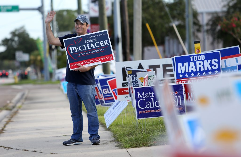 Middle school teacher Robert Pechacek, a candidate for Hillsborough County School Board, waves to motorists Tuesday at the Jan Platt Library on S. Manhattan Ave. in Tampa. [JAMES BORCHUCK | Times]