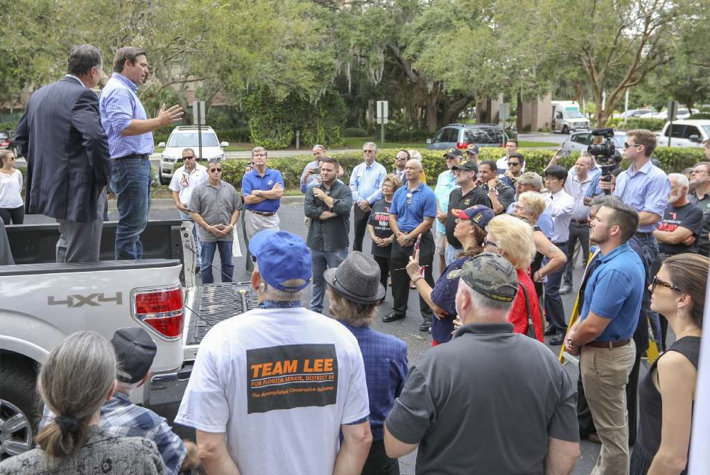 Florida gubernatorial candidate Ron DeSantis, left, speaks to supporters at a Hurricane Michael relief supply drop-off Tuesday. [CHRIS URSO | Tampa Bay Times]