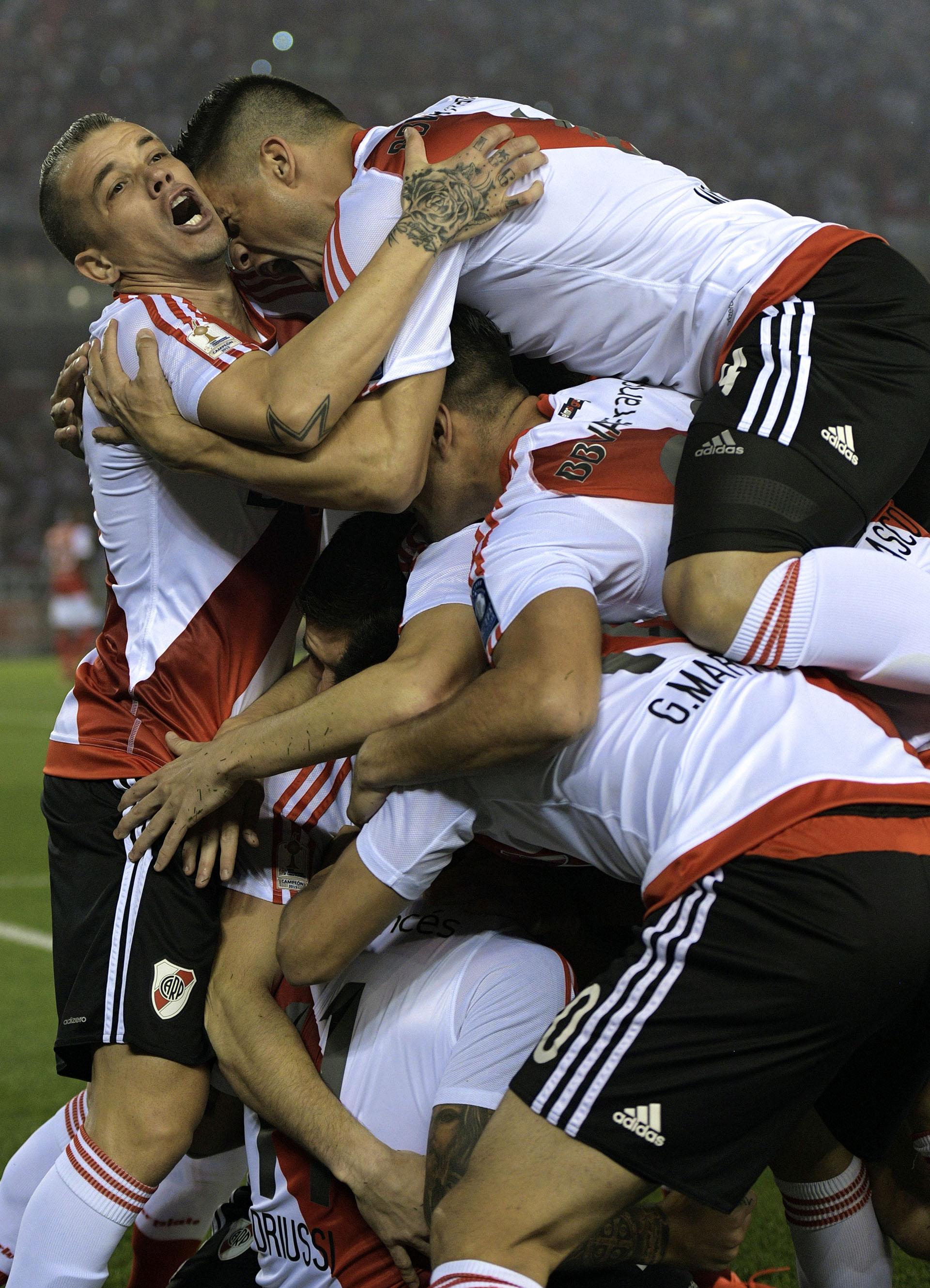 Todos van a abrazar a Driussi, quien quedó tapado, trasel primer gol (AFP)