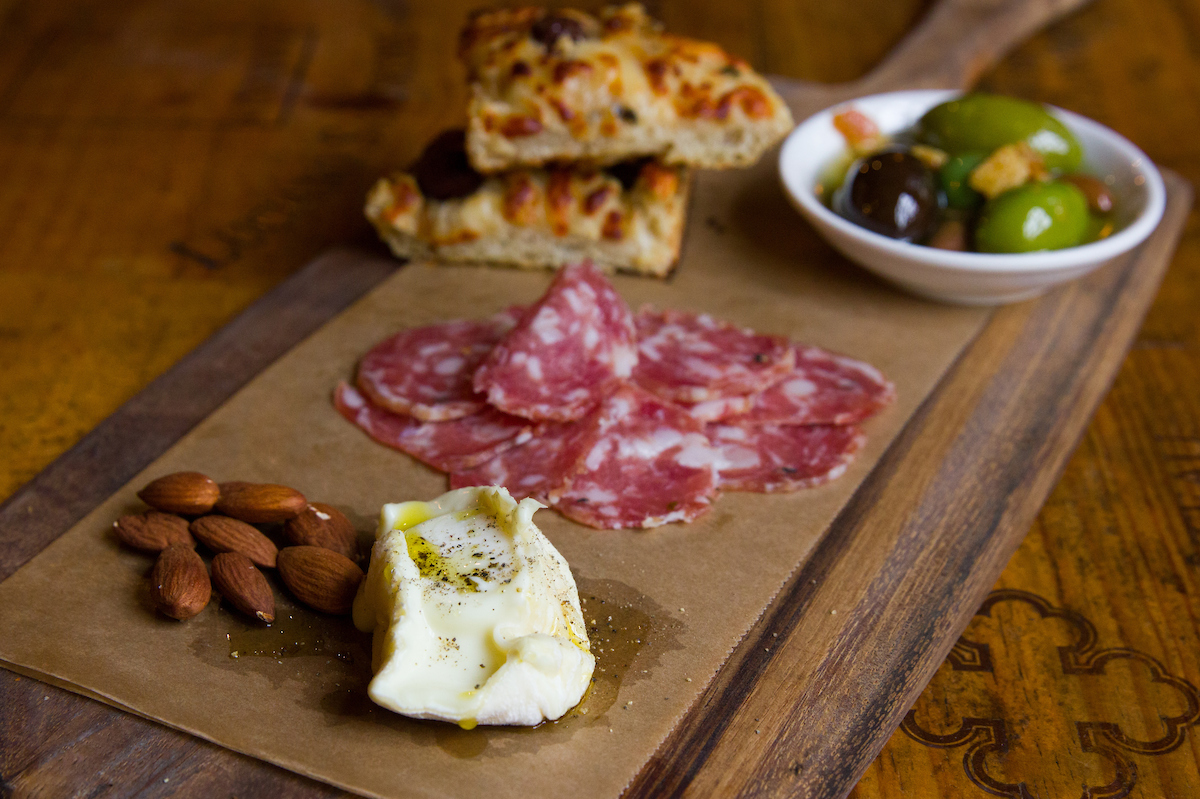 antipasti board with cheese, salami, and olives