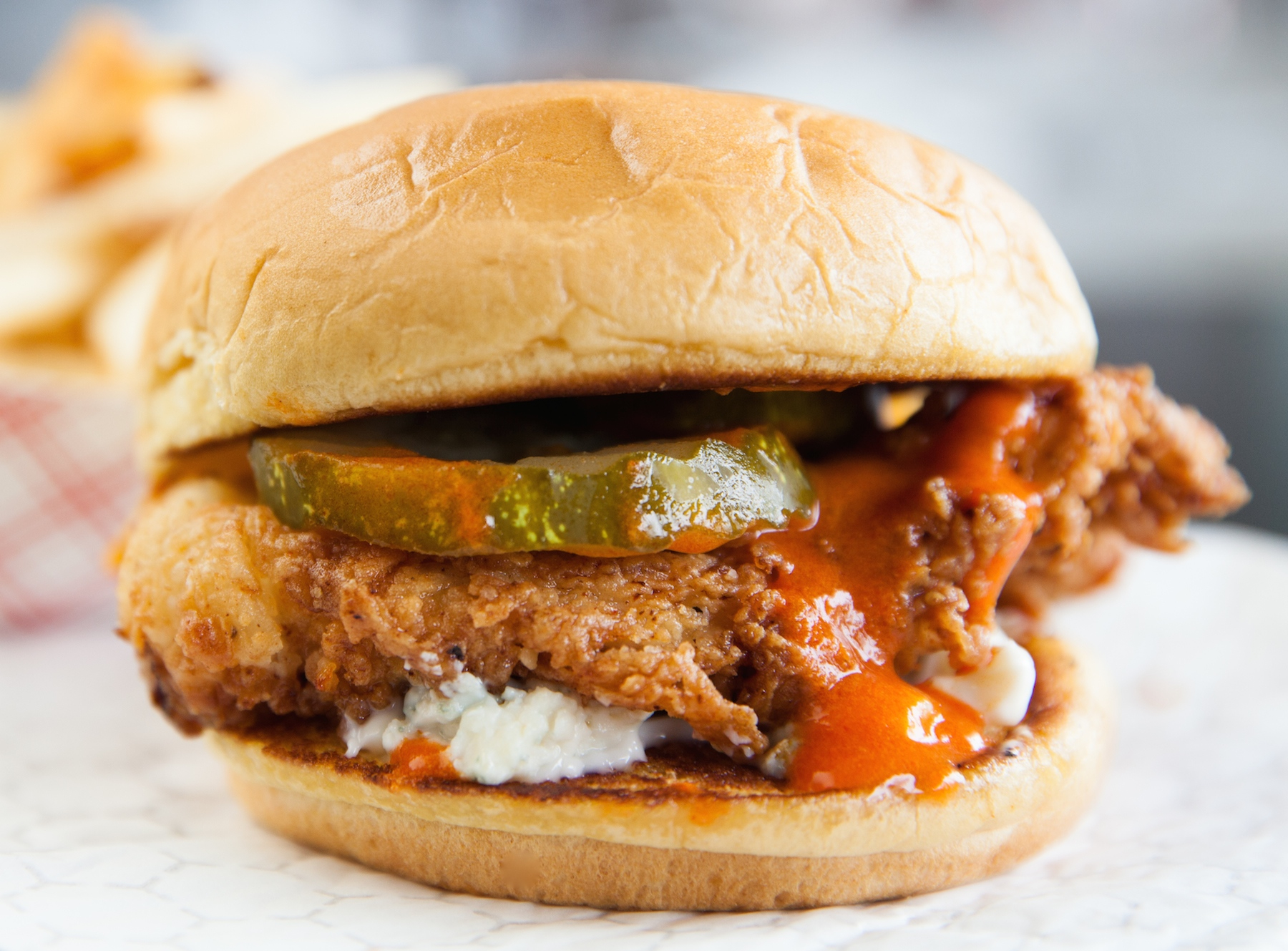 A spicy chicken sandwich side view with the pickles and hot sauce
