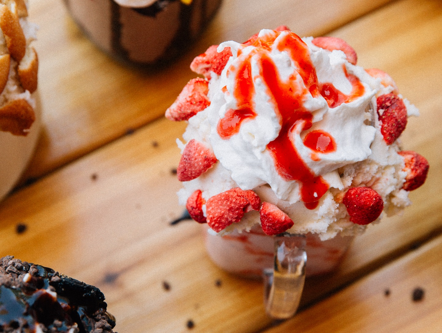 A strawberry milkshake covered in shipped cream and strawberries on top