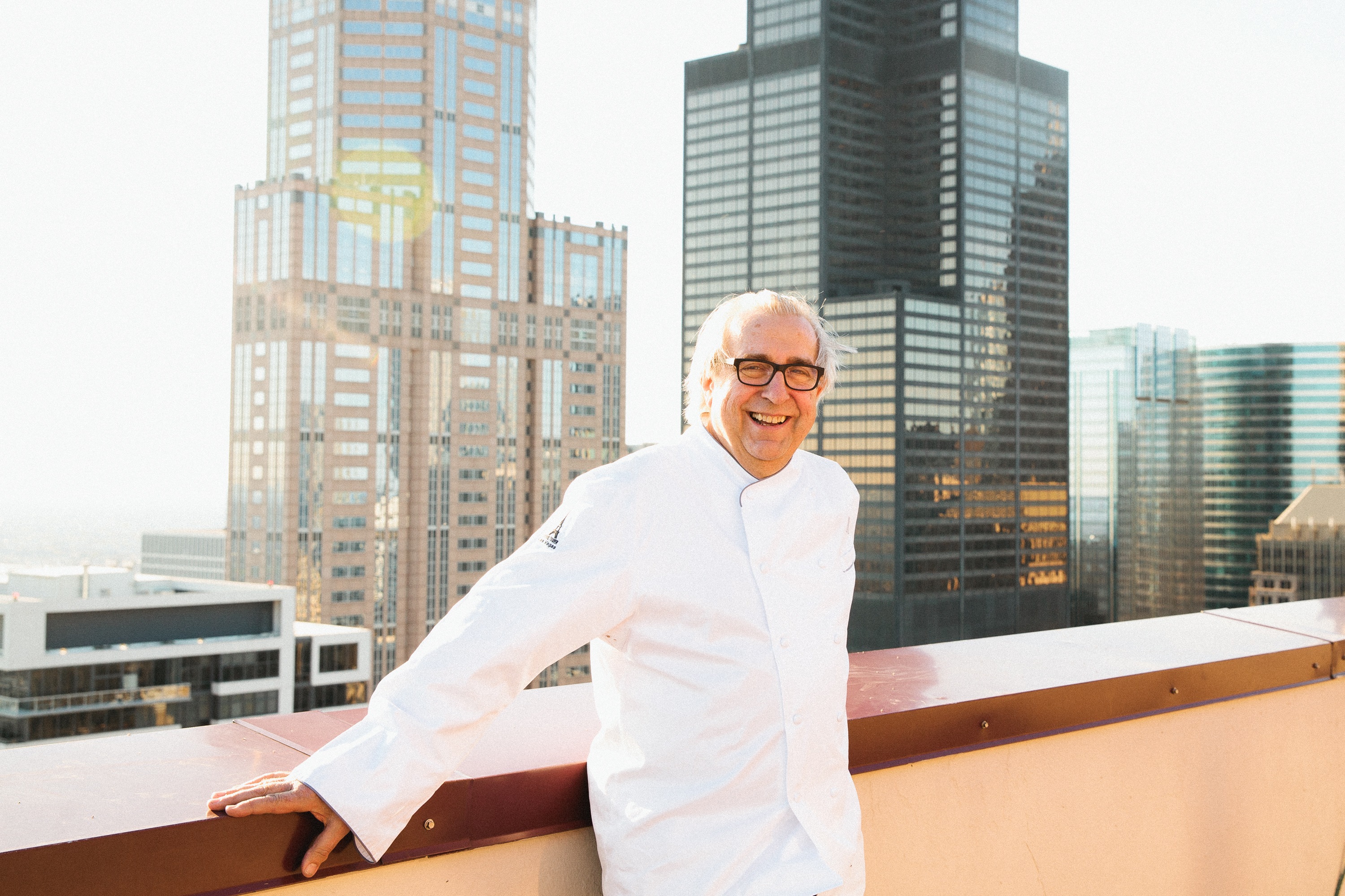 Chef Jean Joho standing outside with the city skyline behind him