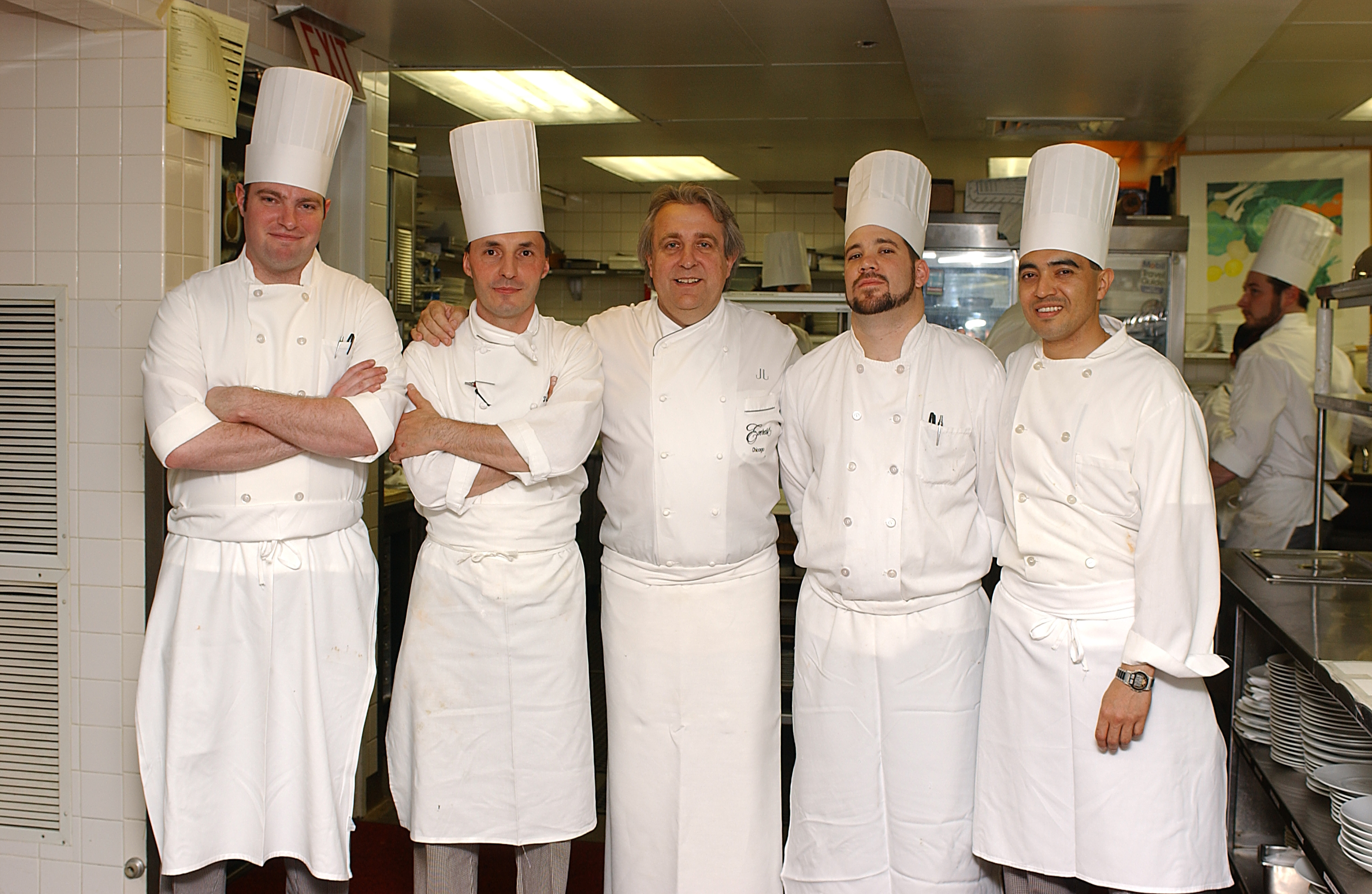 A line of chefs in the kitchen of Everest with Joho in the middle with his arms around him
