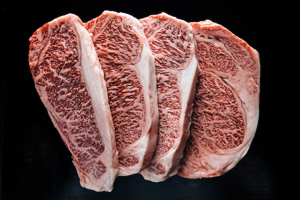 raw wagyu steaks on black background