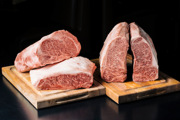 raw wagyu steaks on wooden blocks